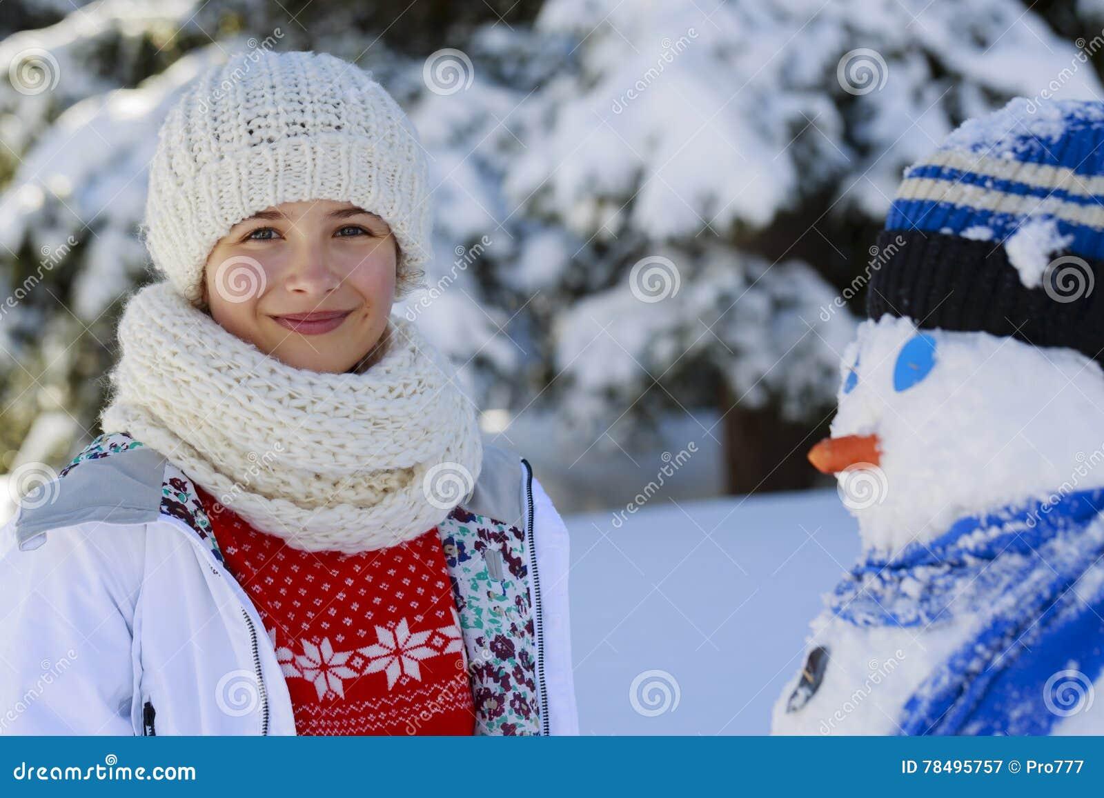 Το ευτυχές παιχνίδι έφηβη χαμόγελου με έναν χιονάνθρωπο σε έναν χιονώδη κερδίζει