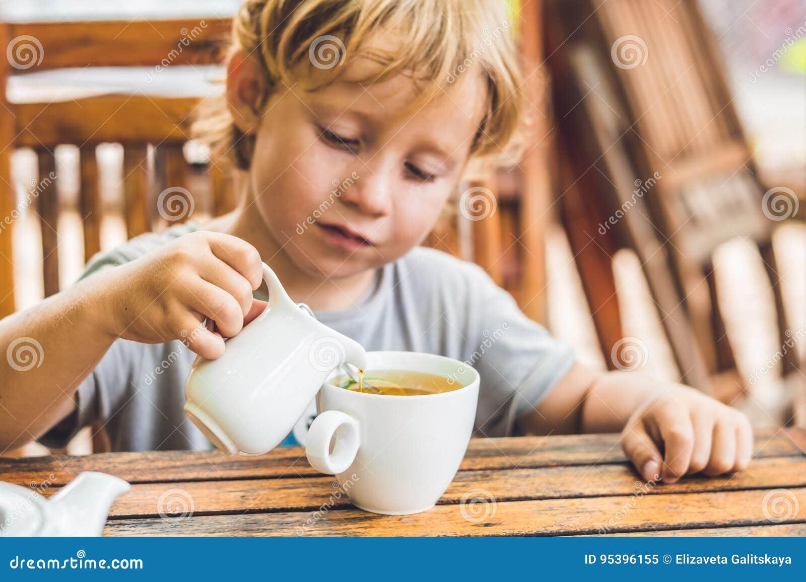 Το ευτυχές συμπαθητικό αγόρι χύνει το μέλι στο τσάι στο θερινό πράσινο κήπο Πορτρέτο υπαίθριος