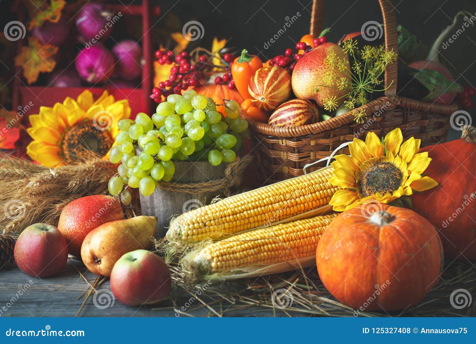 Το ευτυχές υπόβαθρο ημέρας των ευχαριστιών, ο ξύλινος πίνακας που διακοσμούνται με τις κολοκύθες, ο αραβόσιτος, τα φρούτα και το