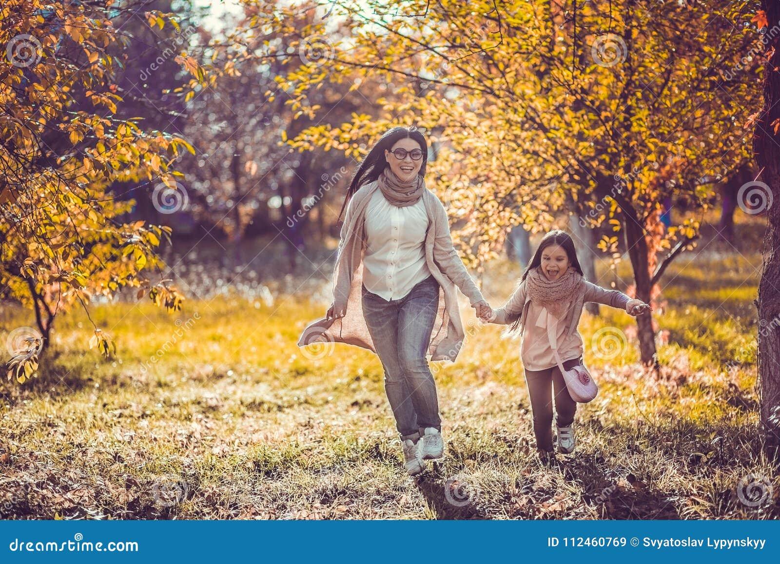 Το ευτυχές mum και η κόρη παίζουν το πάρκο φθινοπώρου