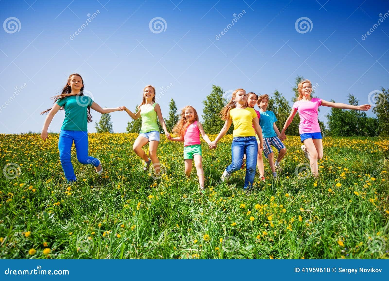 Το ευτυχείς τρέξιμο και η λαβή παιδιών παραδίδουν το πράσινο λιβάδι