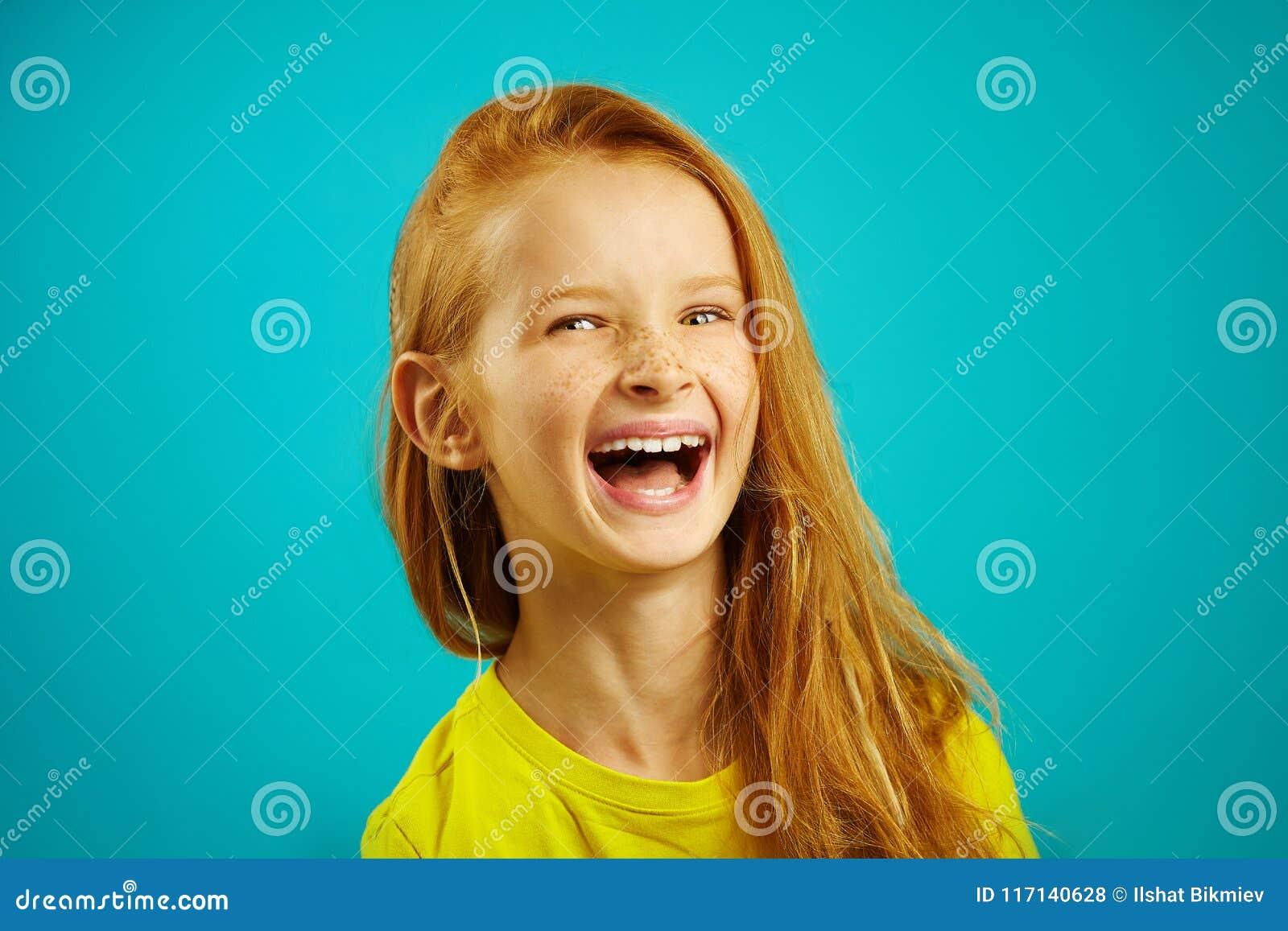 Το εύθυμο μικρό κορίτσι γελά μια ειλικρινής έκφραση των συναισθημάτων, πορτρέτο του ευτυχούς παιδιού στο μπλε υπόβαθρο