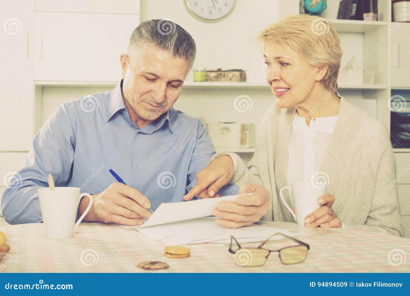 Το εύθυμο ώριμο ζεύγος στον πίνακα μελετά προσεκτικά τα έγγραφα
