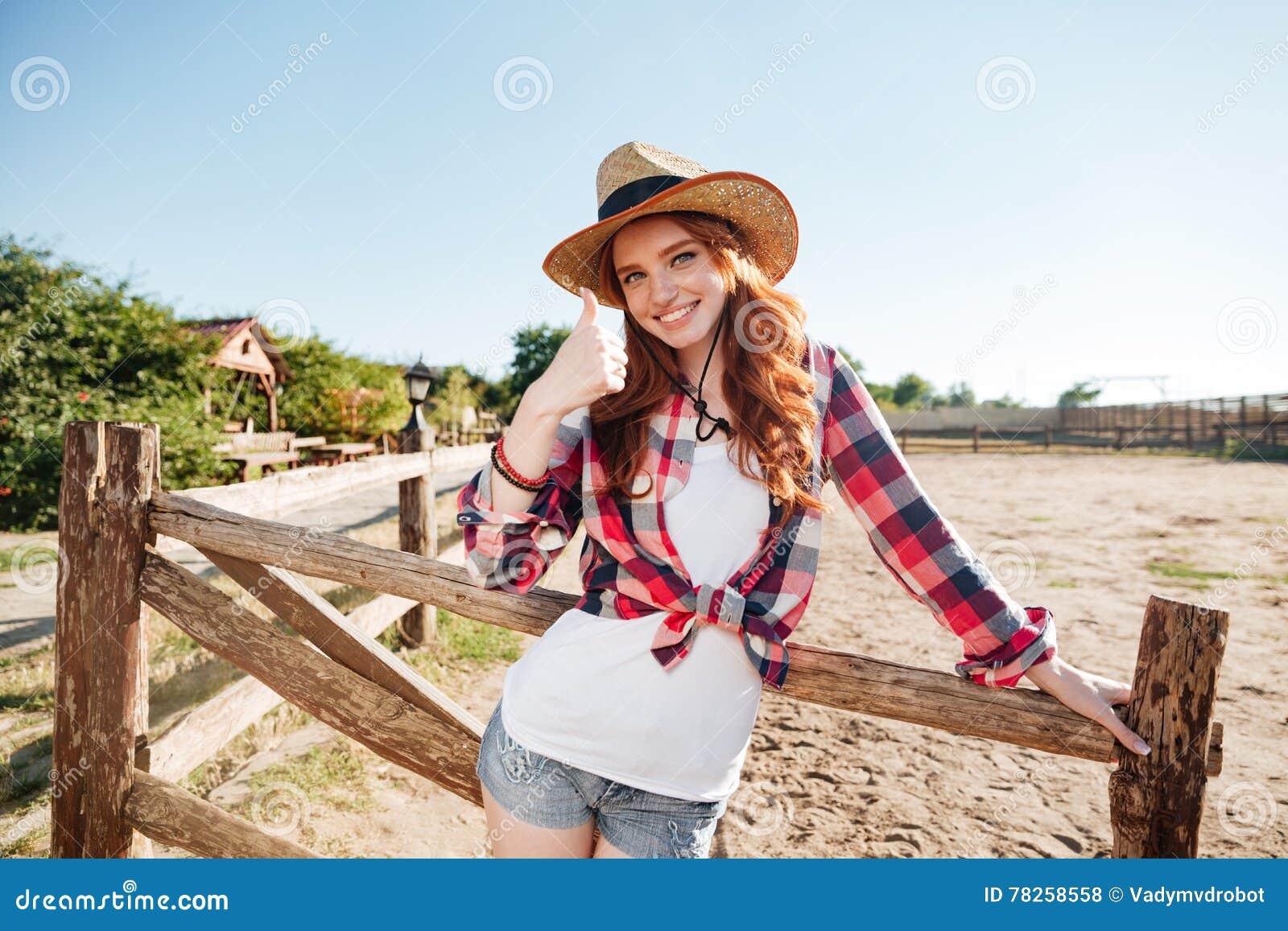 Το εύθυμο redhead cowgirl χαμόγελου στην παρουσίαση καπέλων φυλλομετρεί επάνω τη χειρονομία