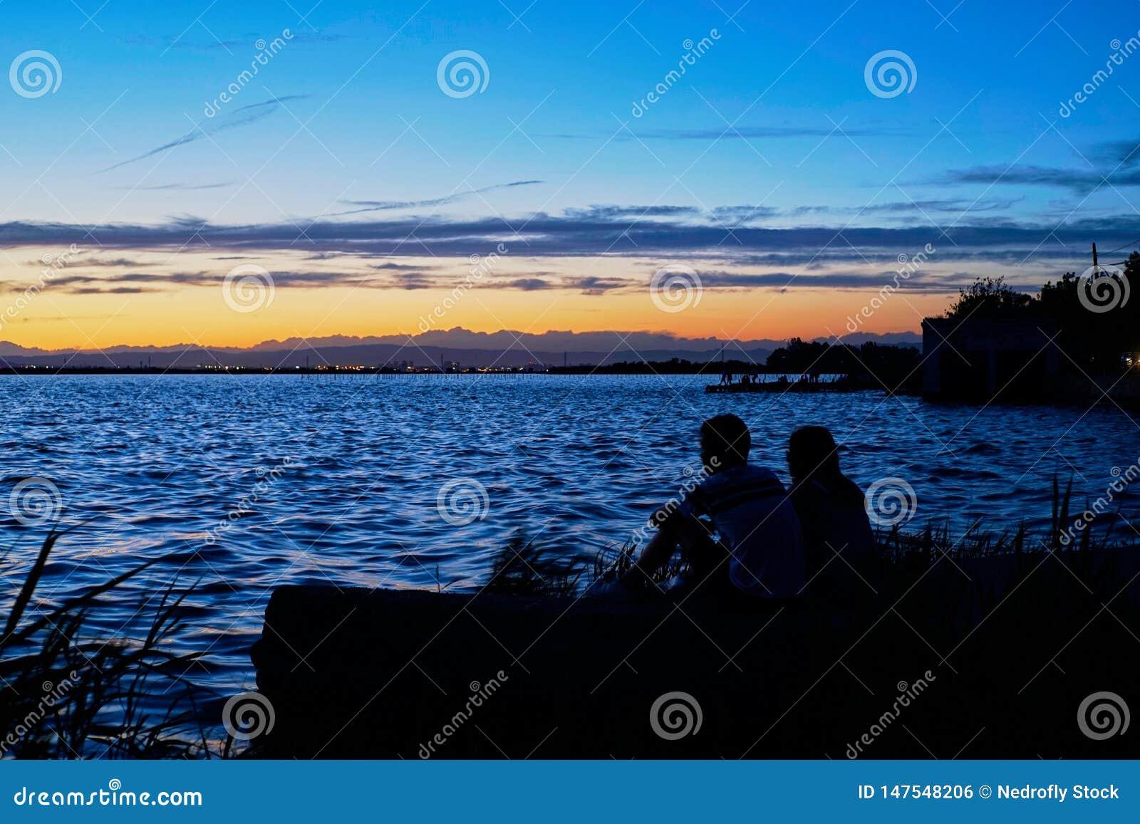 Το ζεύγος ερωτευμένο συλλογίζεται το ηλιοβασίλεμα στο Albufera της Βαλένθια