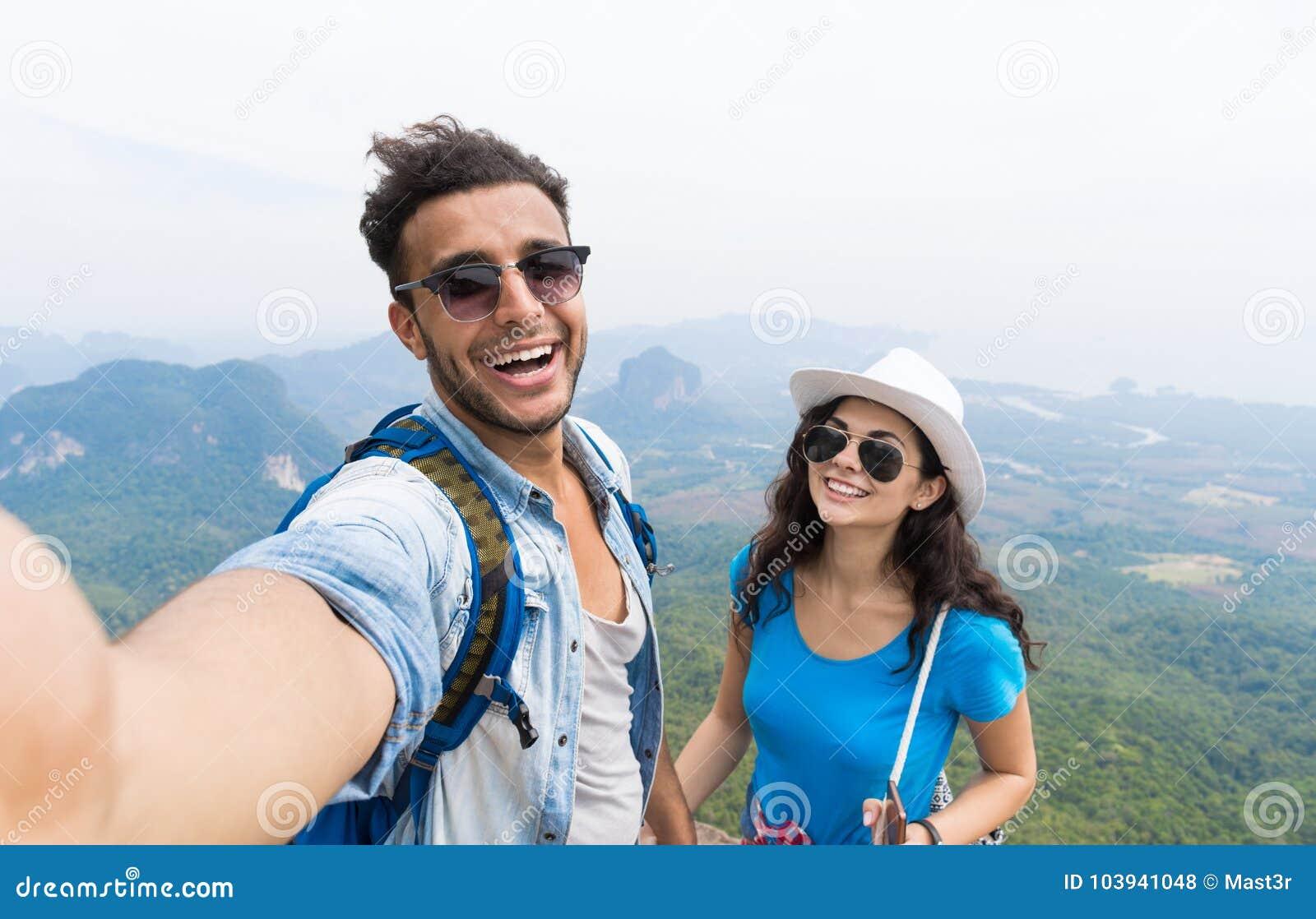 Το ζεύγος με τα σακίδια πλάτης παίρνει τη φωτογραφία Selfie πέρα από την οδοιπορία τοπίων βουνών, το νεαρό άνδρα και τη γυναίκα σ