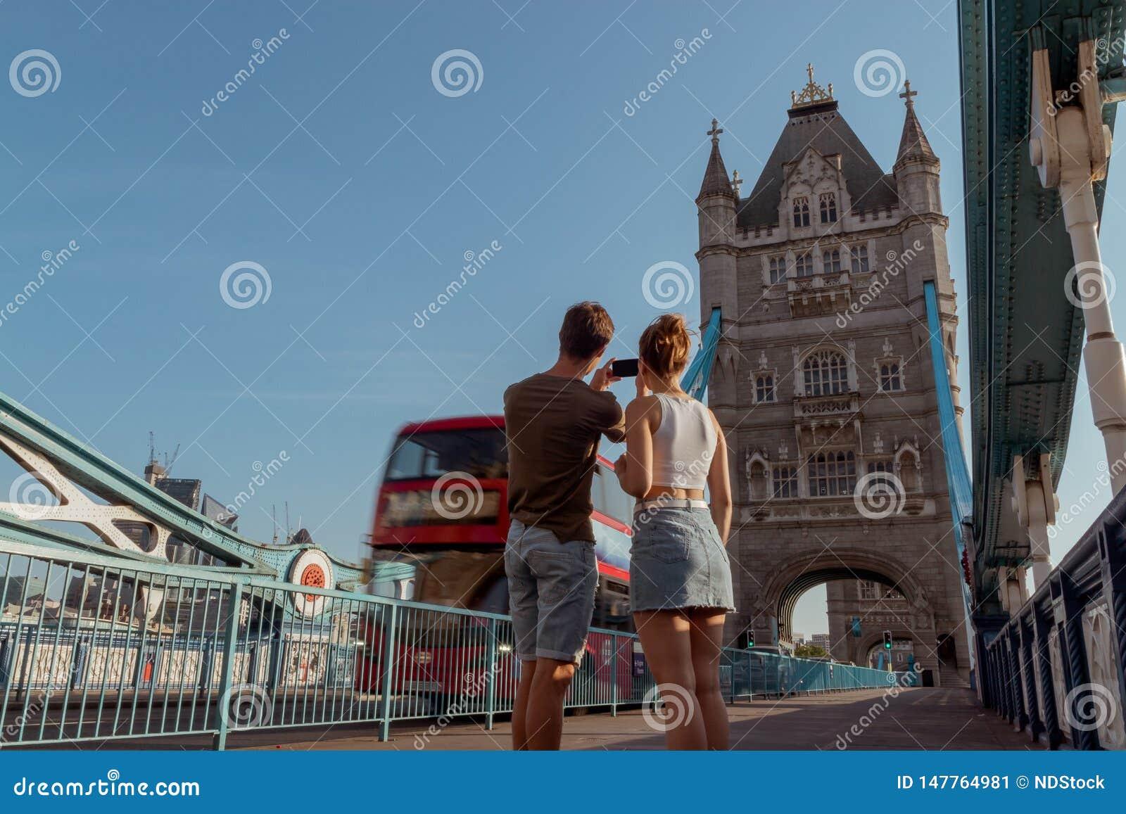 Το ζεύγος παίρνει μια εικόνα ενός κόκκινου διπλού λεωφορείου καταστρωμάτων στη γέφυρα πύργων στο Λονδίνο