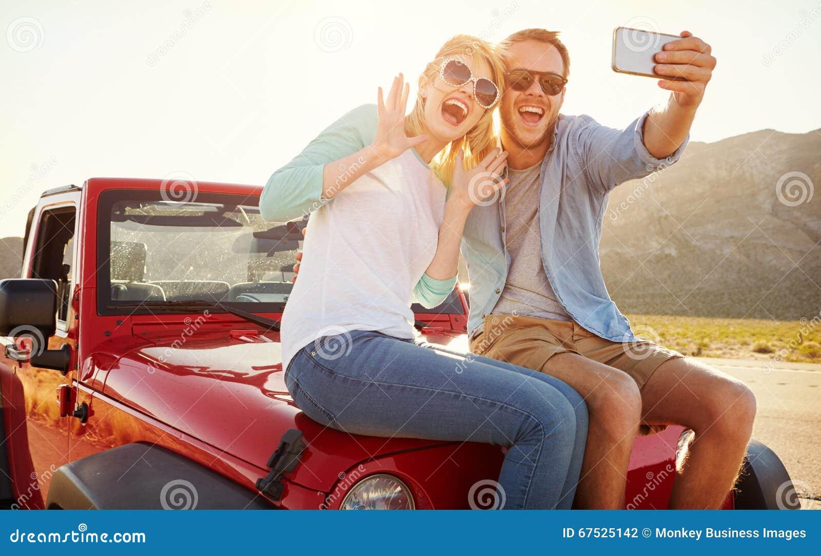 Το ζεύγος στο οδικό ταξίδι κάθεται στο μετατρέψιμο αυτοκίνητο που παίρνει Selfie