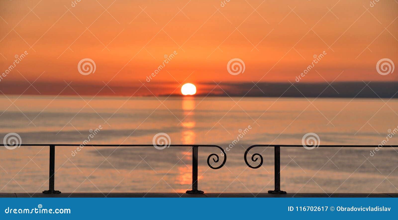 Το ζωηρόχρωμο θερμό πορτοκαλί ηλιοβασίλεμα στη θάλασσα Mediteranian κοίταξε από το σταθμό τρένου σε Manarola, Cinque Terre στη Λι