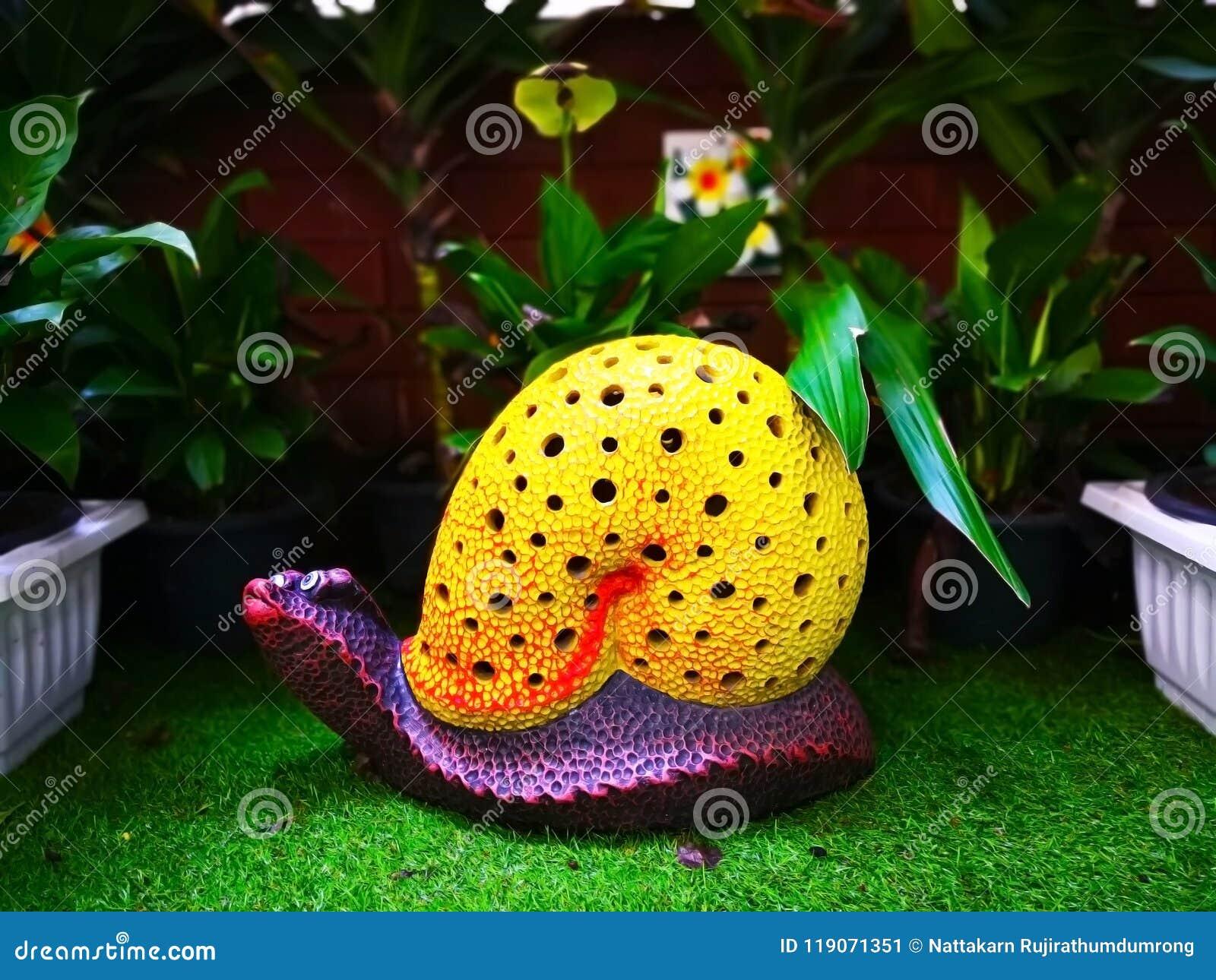 Το ζωηρόχρωμο κεραμικό σαλιγκάρι με το κίτρινο κοχύλι και το πορφυρό σώμα, wh