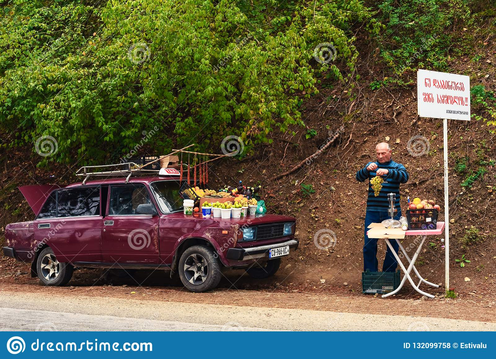 Το ηλικιωμένο άτομο σε μια άκρη του δρόμου κάνει εμπόριο στα φρούτα από το αυτοκίνητο