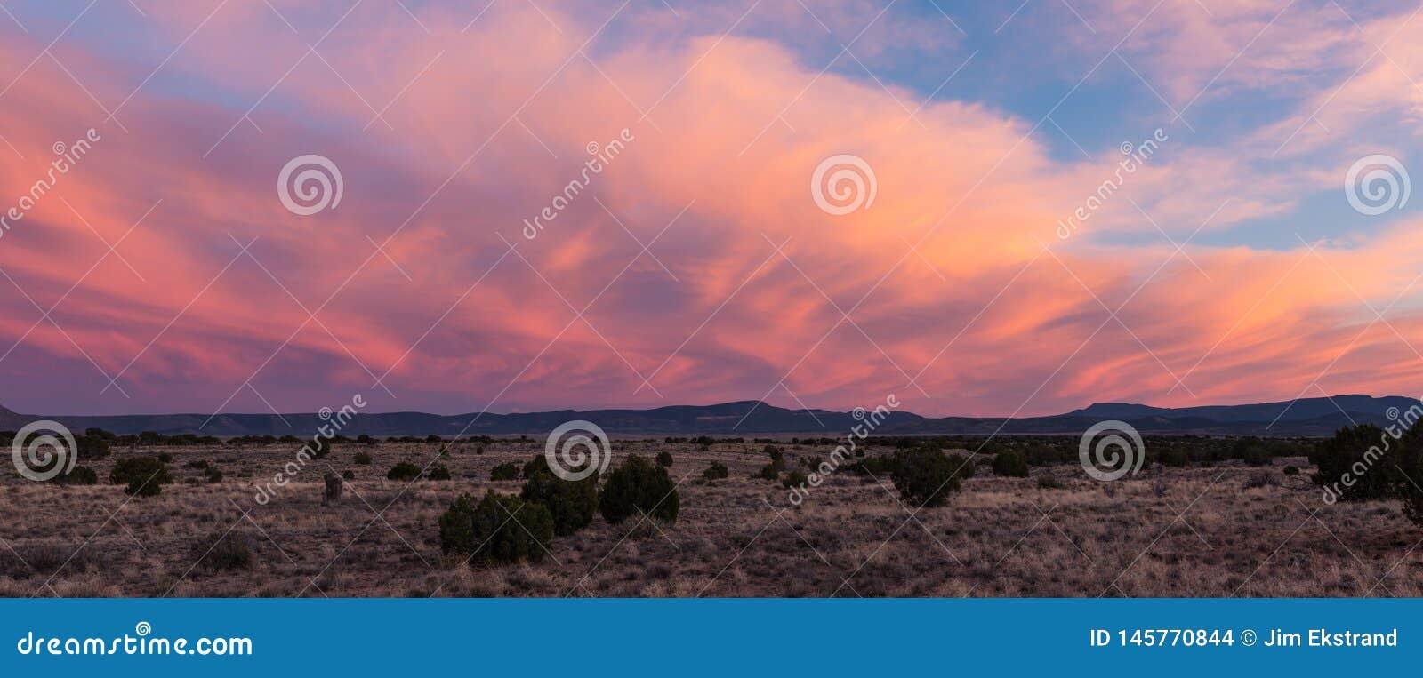 Το ηλιοβασίλεμα φωτίζει τα στροβιλιμένος δραματικά σύννεφα πέρα από ένα τοπίο ερήμων