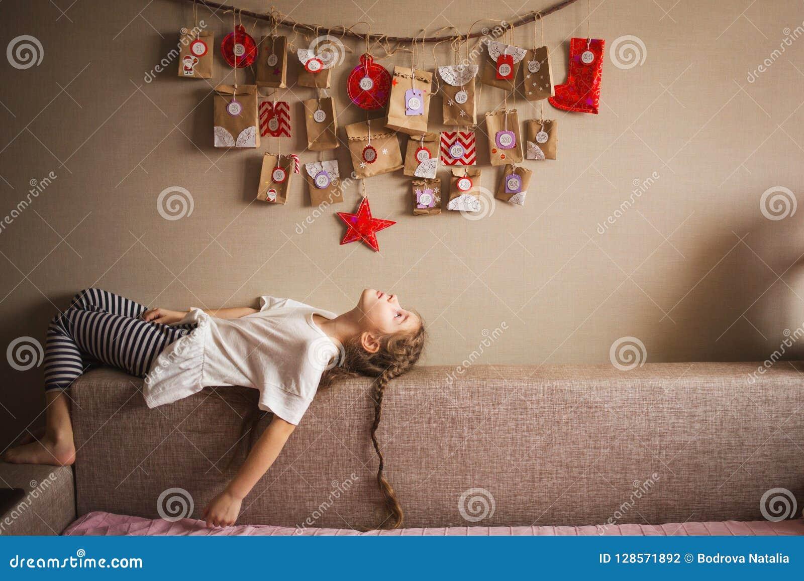 Το ημερολόγιο εμφάνισης που κρεμά στον τοίχο μικρές εκπλήξεις δώρων για τα παιδιά το κορίτσι βρίσκεται και εξετάζει το ημερολόγιο