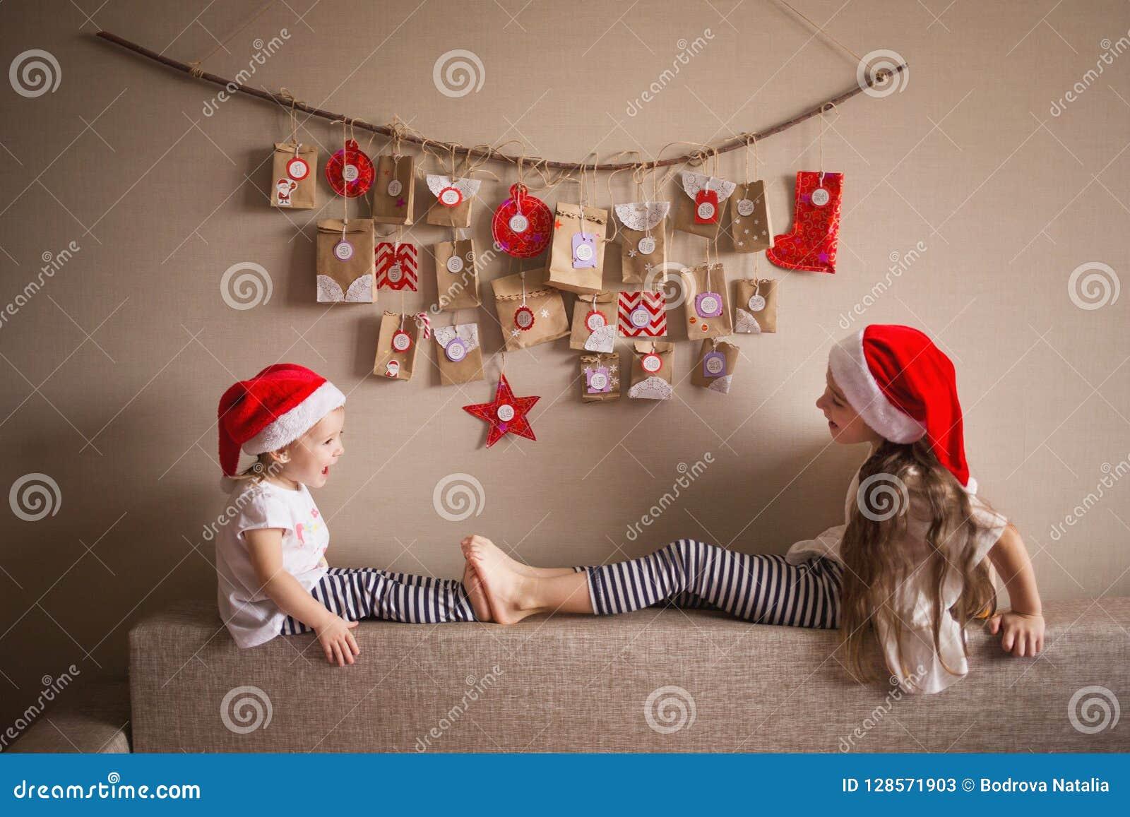 Το ημερολόγιο εμφάνισης που κρεμά στον τοίχο μικρές εκπλήξεις δώρων για τα παιδιά δύο αδελφές έντυσαν καθώς τα στοιχειά παίζουν