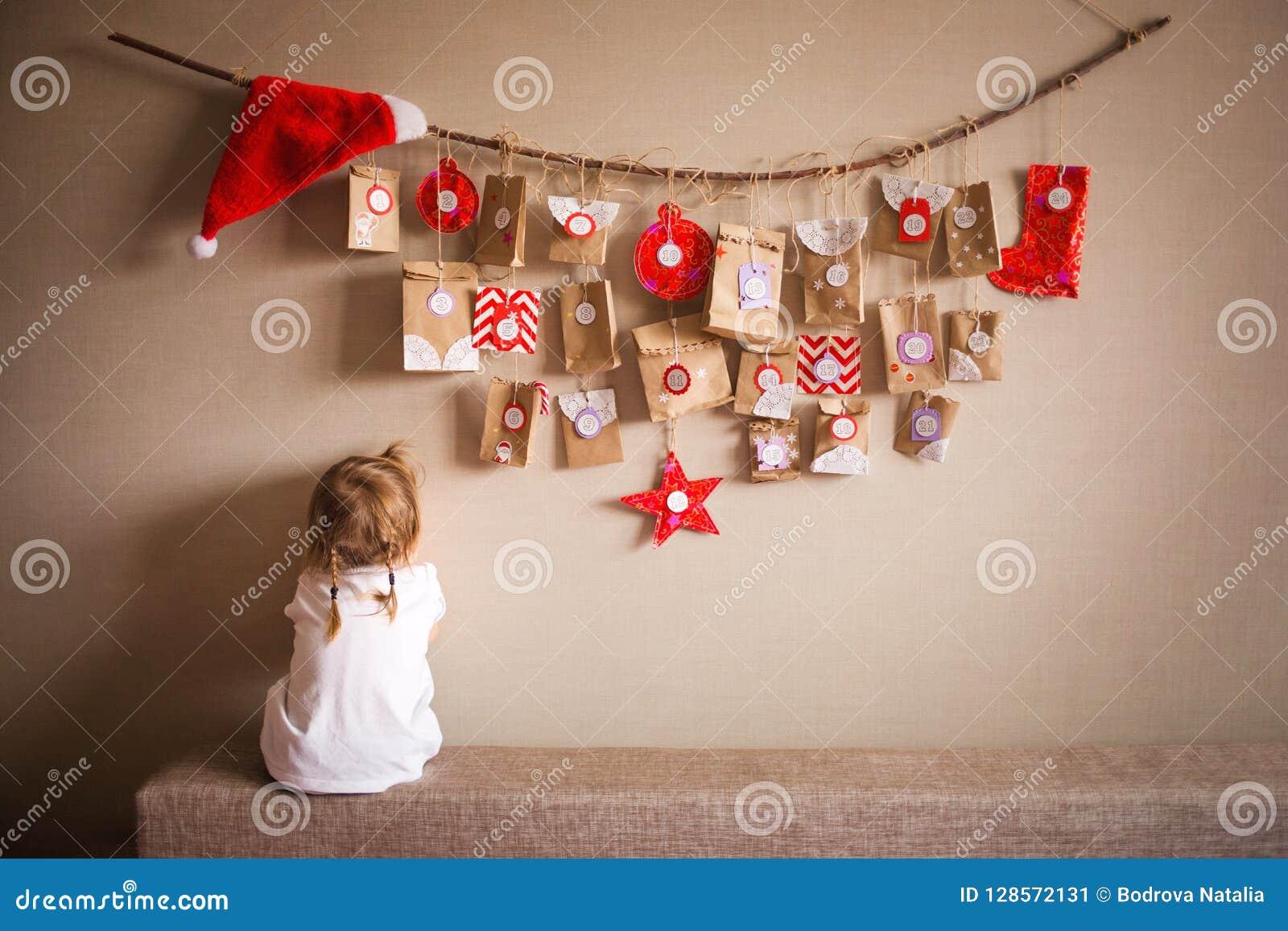 Το ημερολόγιο εμφάνισης που κρεμά στον τοίχο μικρές εκπλήξεις δώρων για τα παιδιά το κορίτσι boo λίγα κρυφοκοιτάζει παίζοντας