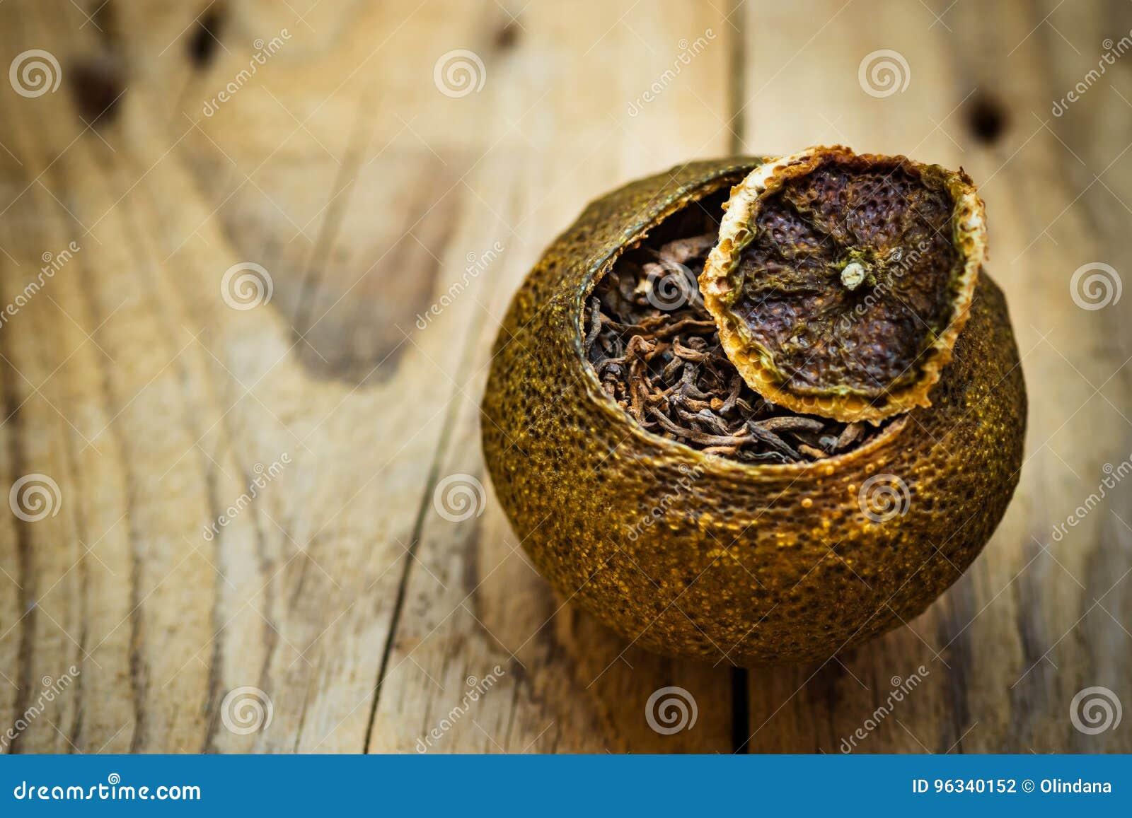 Το ηλικίας ζυμωνομμένο μαύρο κινεζικό τσάι puer σε μια tangerine φλούδα με το καπάκι, ξεπερασμένο ξύλινο υπόβαθρο, κλείνει επάνω