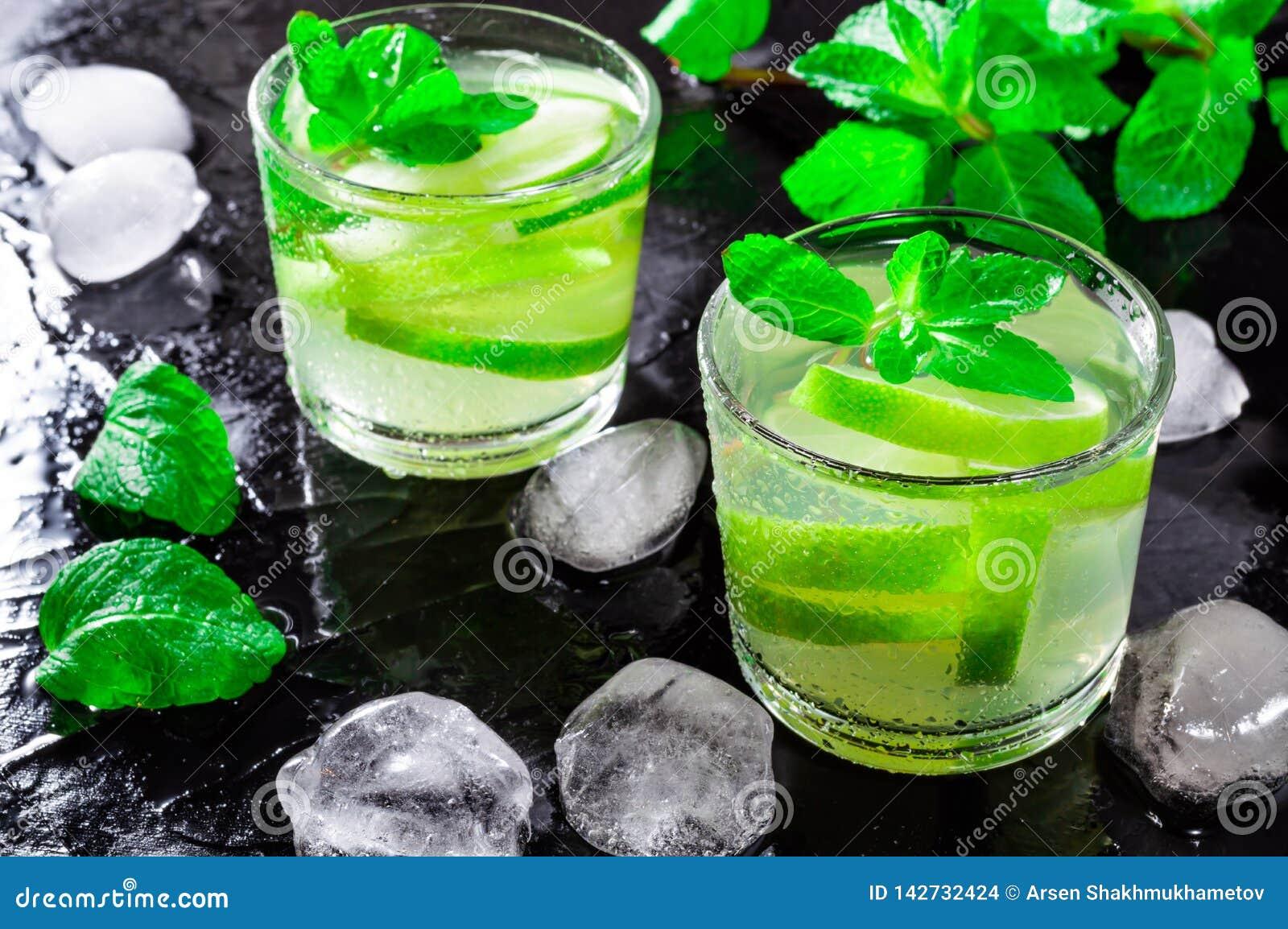 Το θερινό ποτό Mojito, με τους κύβους ασβέστη, μεντών και πάγου, σε ένα μαύρο υπόβαθρο με το νερό μειώνεται