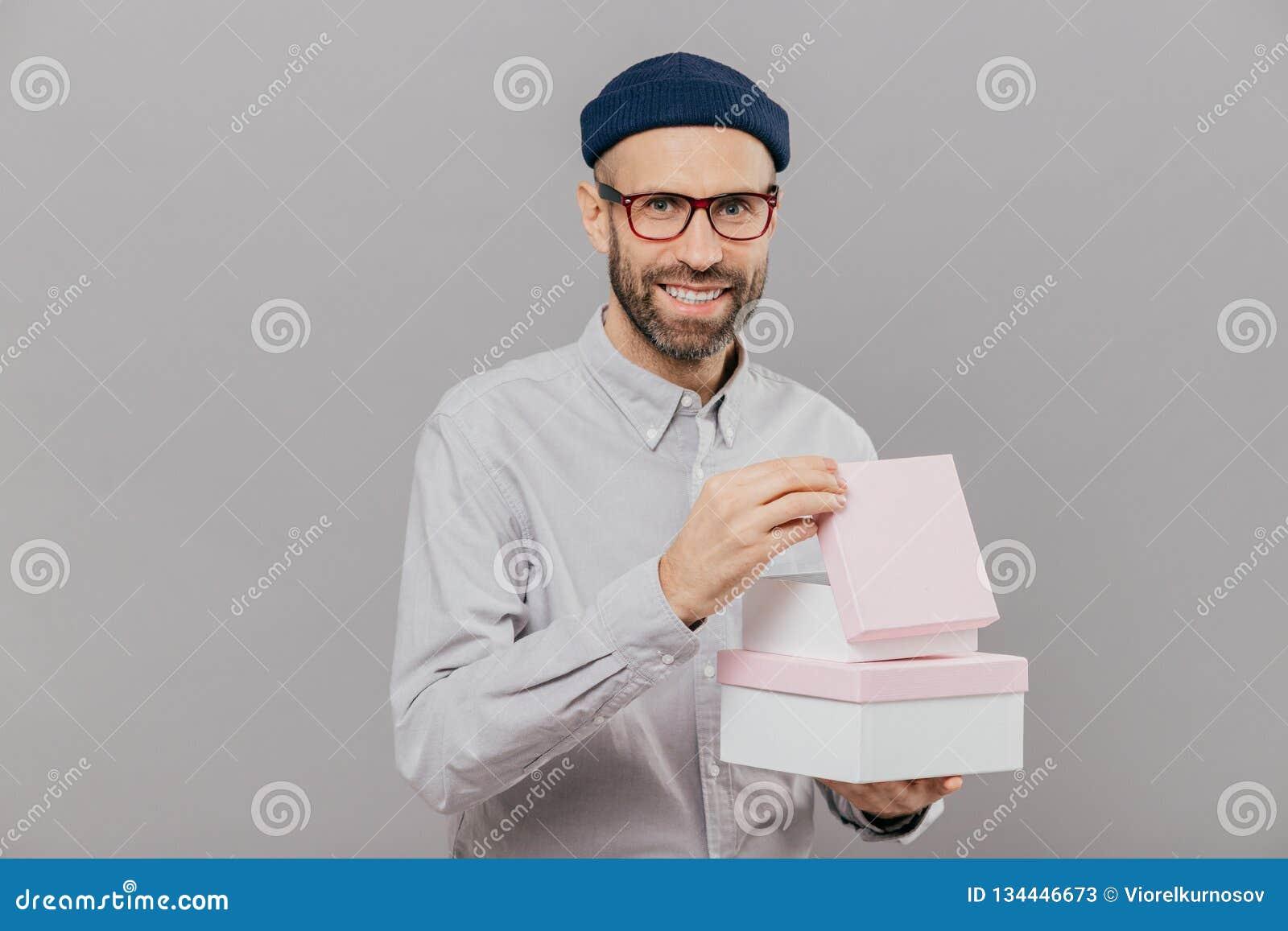 Το θετικό αξύριστο άτομο έχει τις καλαμιές, φέρνει τα κιβώτια με το παρόν, ανοίγει έναν από τους, έχει την ευτυχή έκφραση του προ