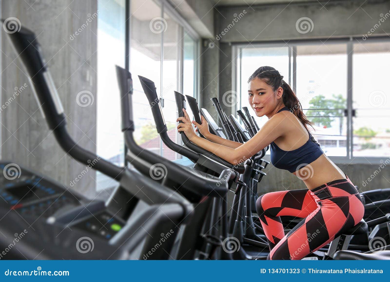 Το θηλυκό ανακυκλώνει στη γυμναστική Πορτρέτο της άσκησης κοριτσιών στις καρδιο μηχανές στην αθλητική λέσχη Όμορφος οικοδόμος σωμ