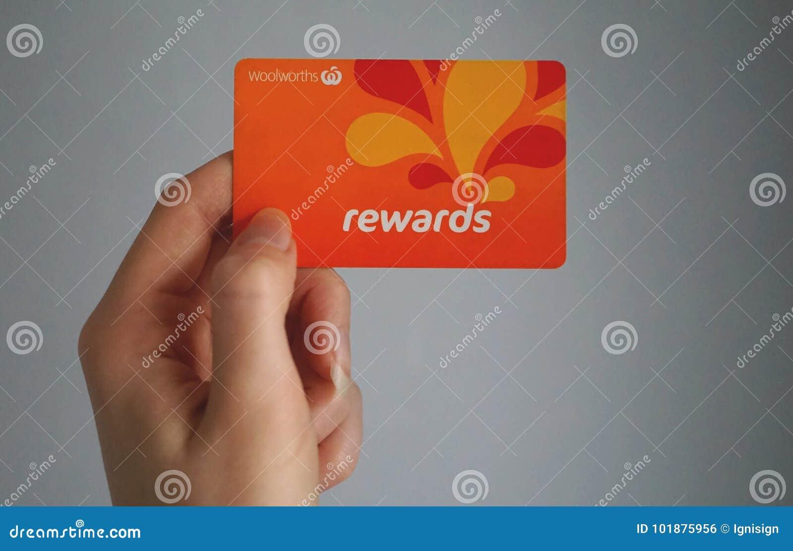 Το θηλυκό καυκάσιο χέρι κρατά ότι ένα Woolworths ανταμείβει την κάρτα πίστης, αυτό το πρόγραμμα πίστης δίνει τα χρήματα από τις α