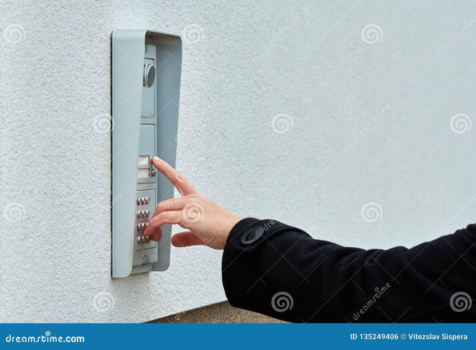 Το θηλυκό χέρι πιέζει ένα κουμπί doorbell με την ενδοσυνεννόηση