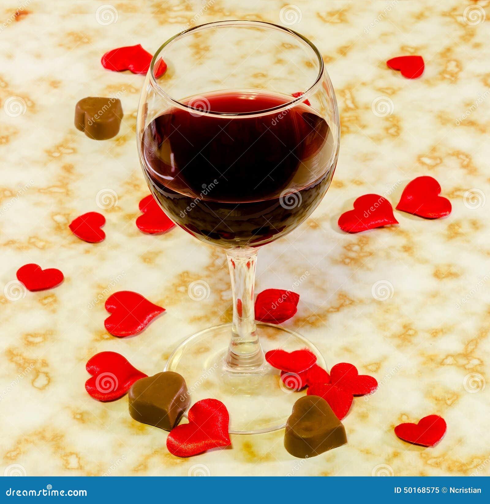 Το διαφανές γυαλί με το κόκκινο κρασί, τη σοκολάτα καρδιών και τις υφαντικές κόκκινες καρδιές βαλεντίνων, παλαιό υπόβαθρο εγγράφο