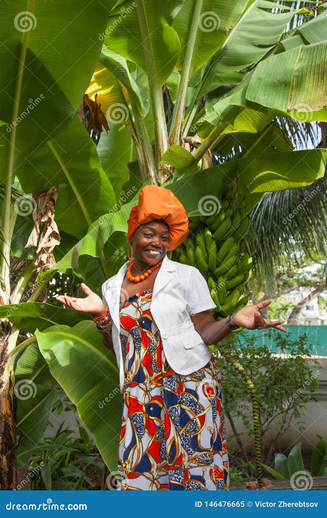 Το κάθετο πλήρες σώμα μιας χαρούμενης γυναίκας αφροαμερικάνων που φορά ένα φωτεινό ζωηρόχρωμο εθνικό φόρεμα θέτει