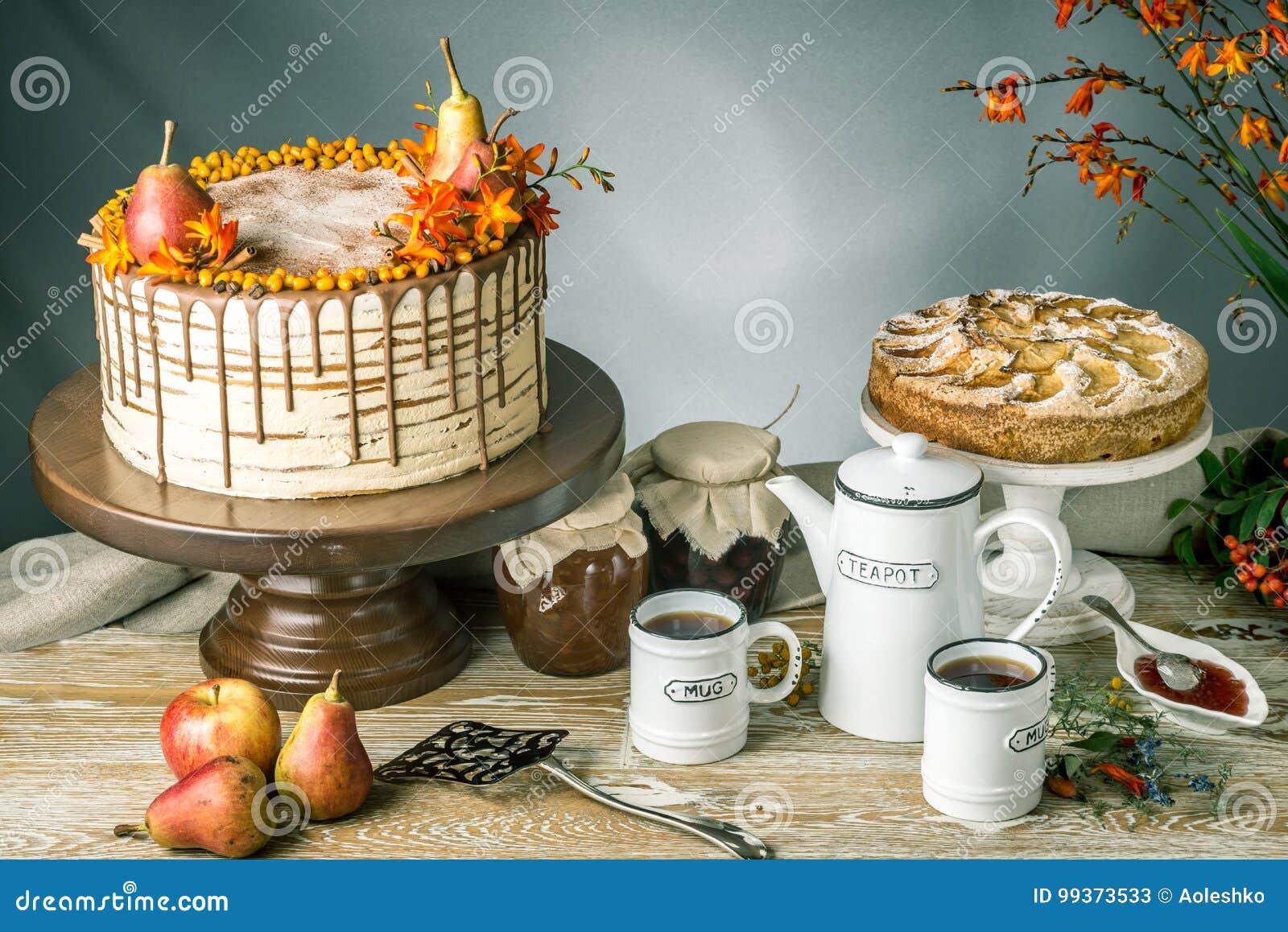 Το κέικ μελιού χύνει πέρα από τη σοκολάτα και διακοσμημένος με τα αχλάδια και τη λευκαγκαθιά σε έναν ξύλινο πίνακα Γλυκιά ζωή φθι