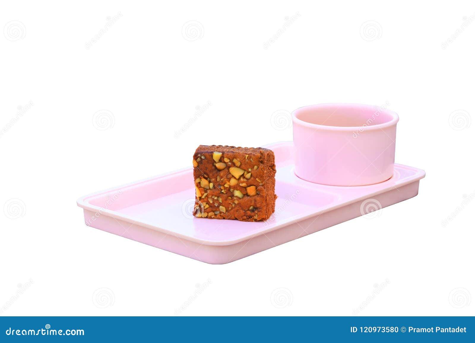 Το κέικ σοκολάτας ψεκάζει με τα καρύδια και το φλυτζάνι καφέ στο ρόδινο πιατάκι απομονωμένος στο άσπρο υπόβαθρο