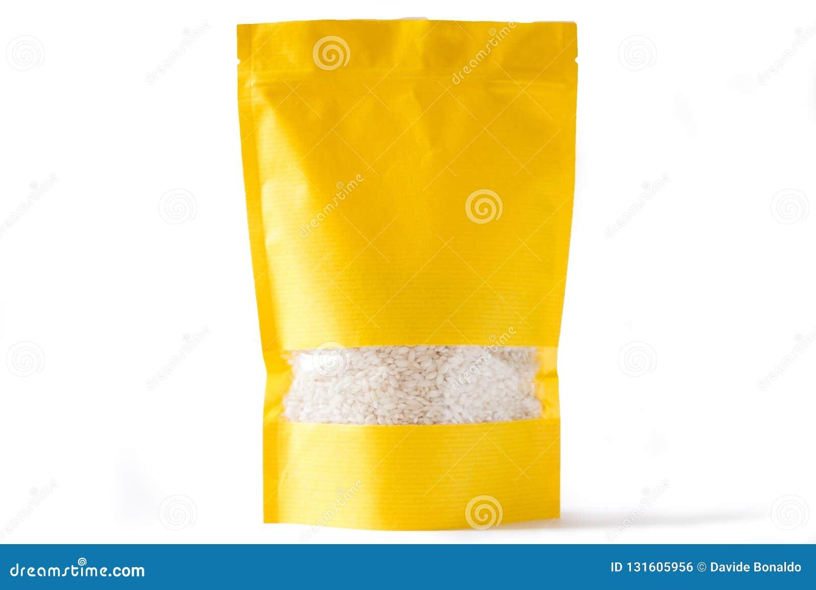 Το κίτρινο έγγραφο doypack στέκεται επάνω τη βιο σακούλα με το φερμουάρ παραθύρων στο άσπρο υπόβαθρο που γεμίζουν με το ρύζι