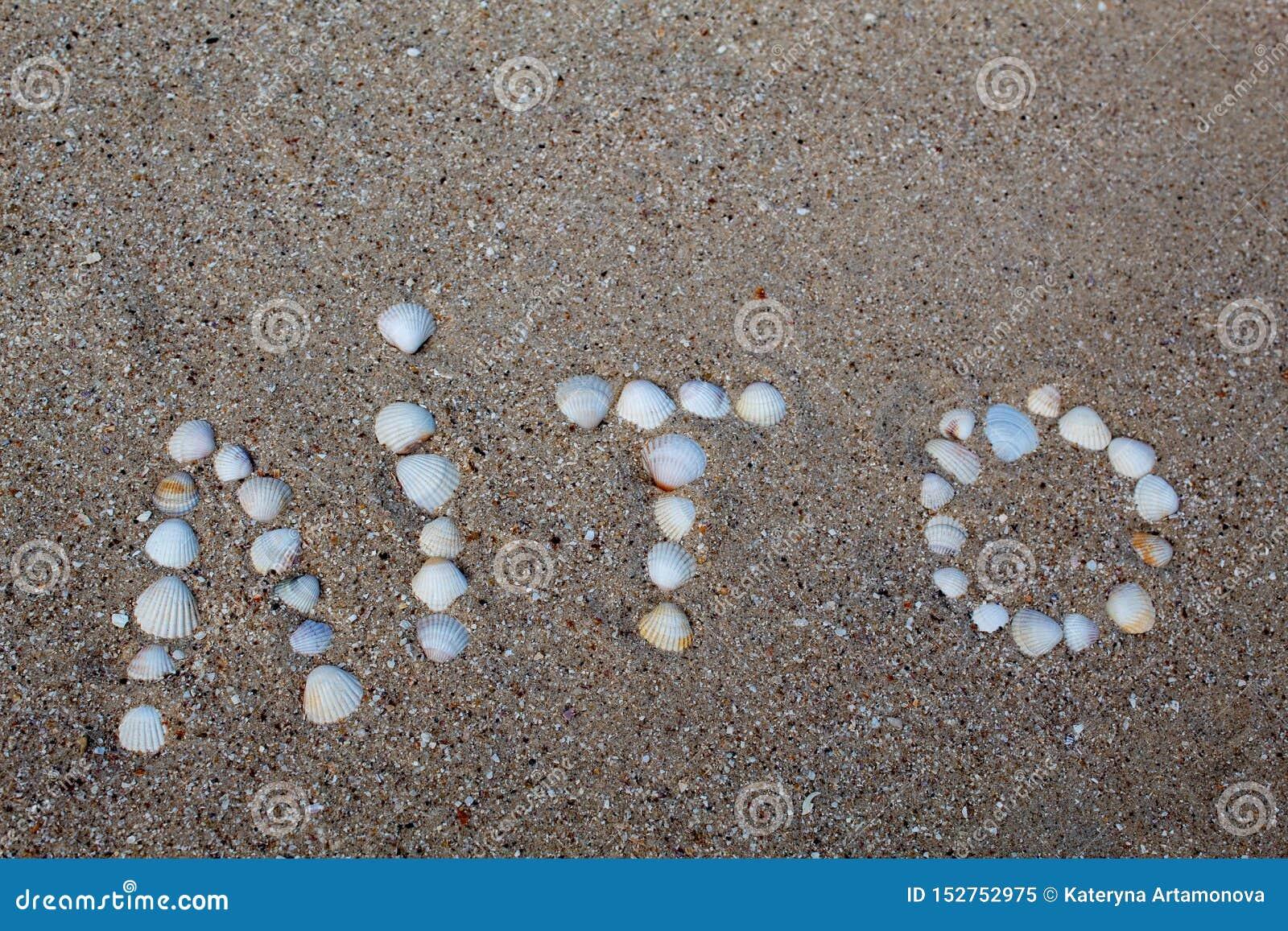 Το καλοκαίρι λέξης, που σχεδιάζεται στην άμμο με τα κοχύλια, στην ουκρανική γλώσσα