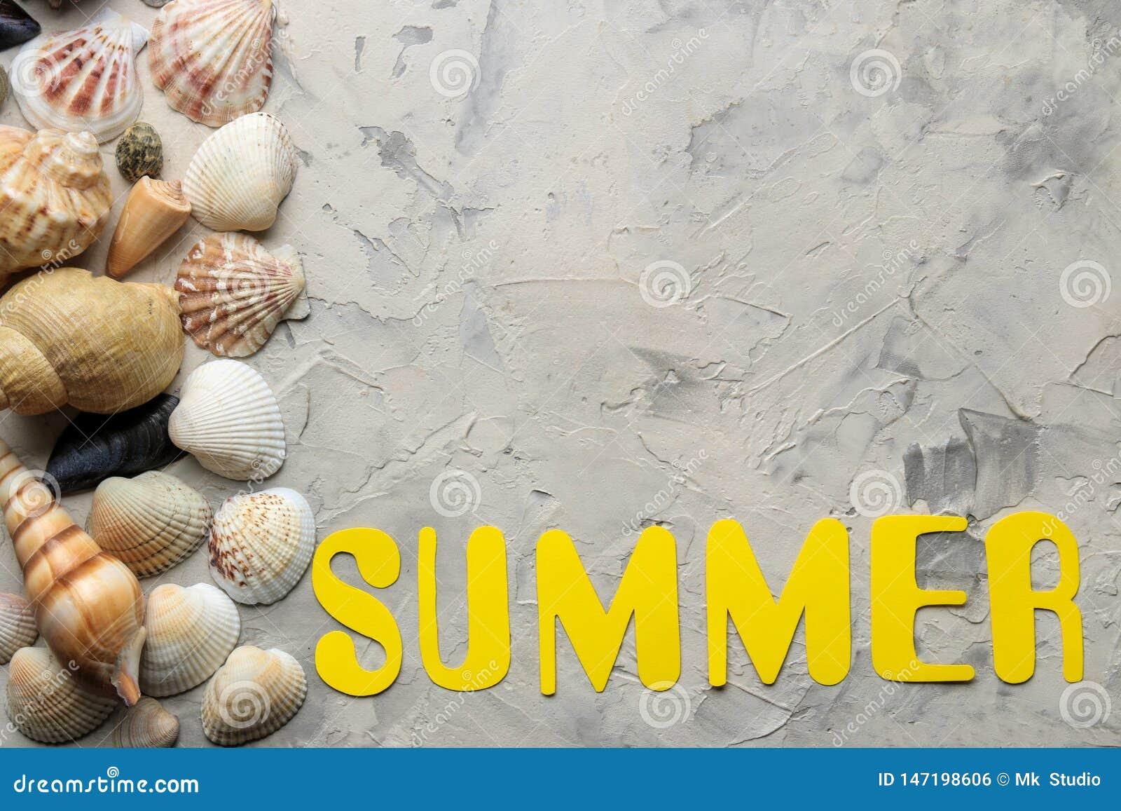 Το καλοκαίρι λέξης των κίτρινων επιστολών εγγράφου και των εξαρτημάτων θάλασσας, κοχύλια σε ένα ελαφρύ συγκεκριμένο υπόβαθρο o r