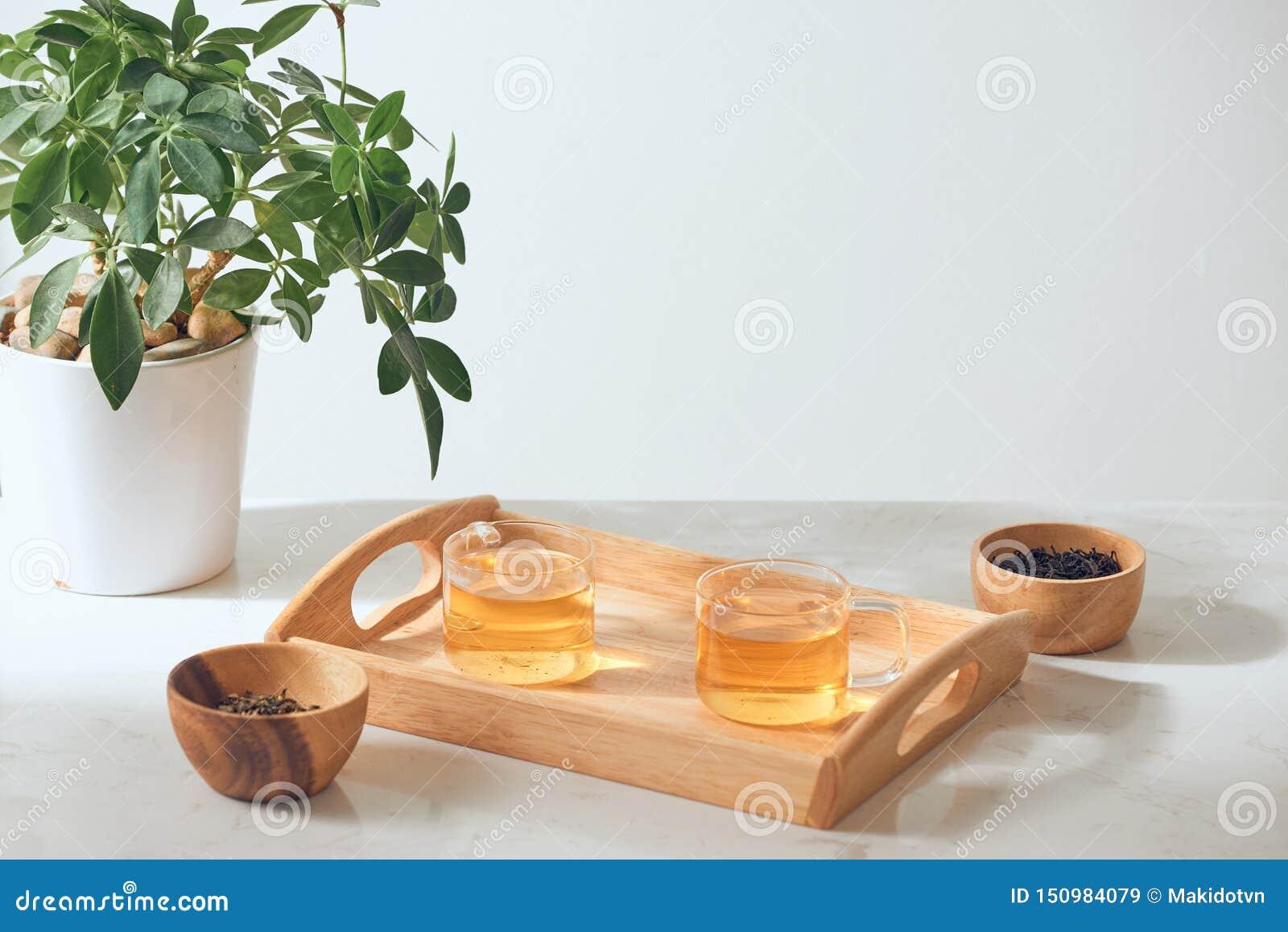 Το καυτό τσάι είναι στο γυαλί Τοποθετημένος σε έναν ξύλινο δίσκο