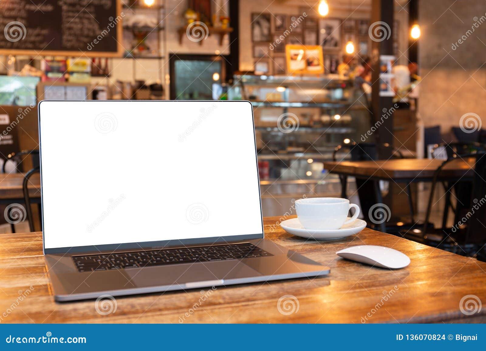 Το κενό lap-top οθόνης με το φλυτζάνι ποντικιών και καφέ στον ξύλινο πίνακα στο coffe ψωνίζει