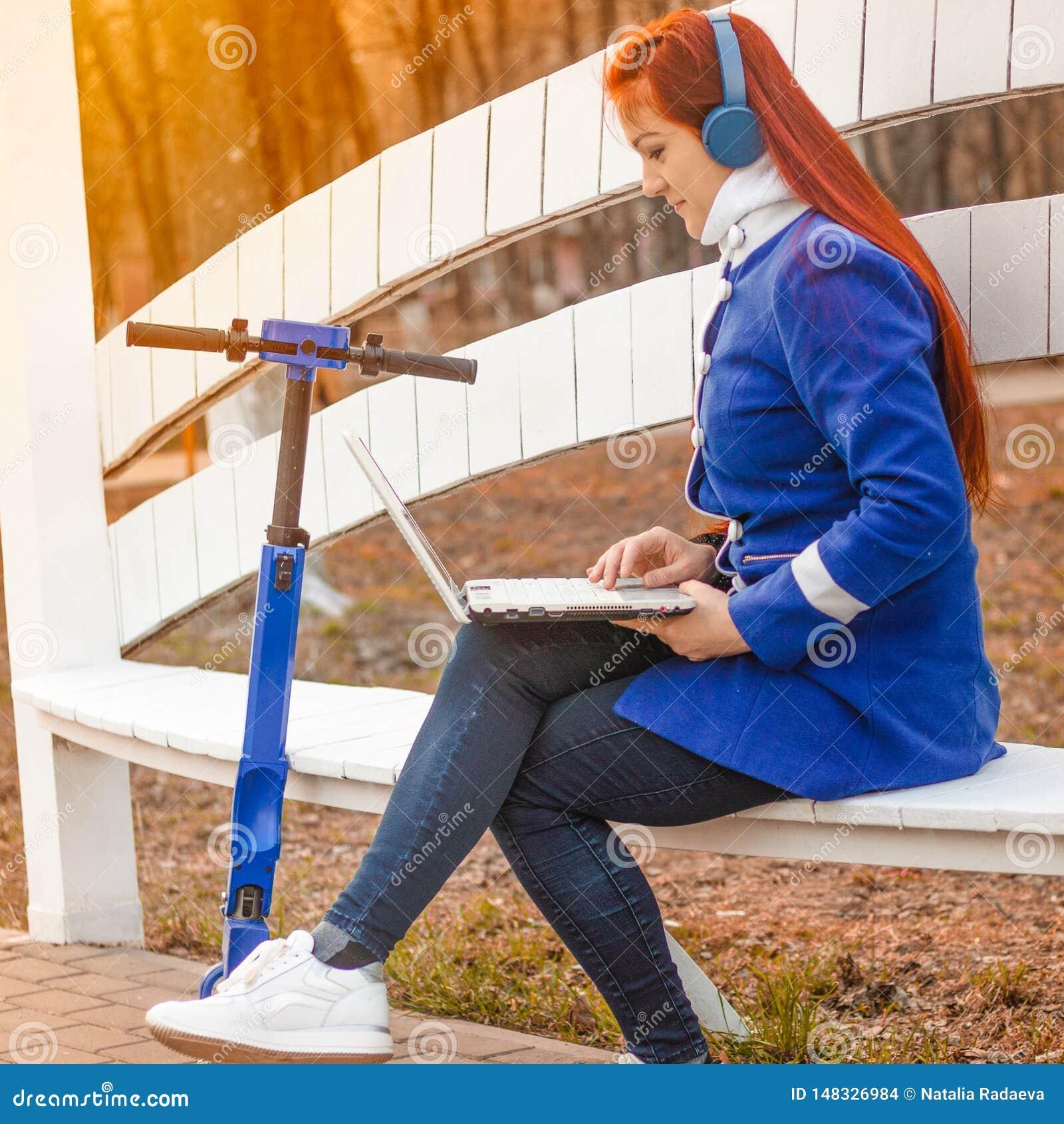 Το κοκκινομάλλες καυκάσιο κορίτσι σε ένα μπλε παλτό εξετάζει το lap-top καθμένος σε έναν πάγκο πάρκων στο ηλιοβασίλεμα Μια νέα γυ