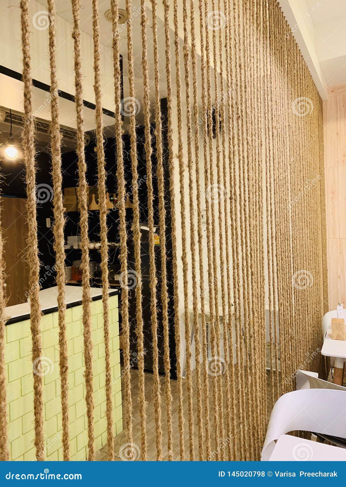 Το κομψό δωμάτιο, που διαιρεί το δωμάτιο με το σχοινί, διακοσμεί
