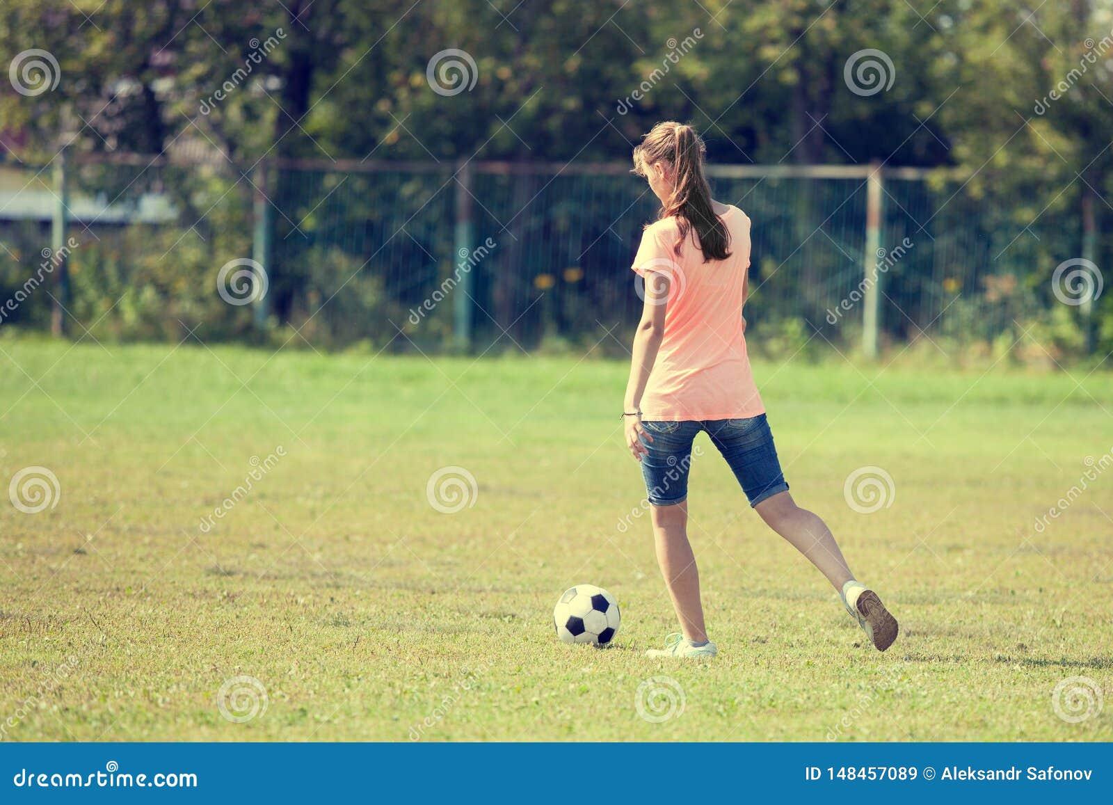Το κορίτσι αθλητών κλωτσά το παιγμένο σφαίρα ποδόσφαιρο