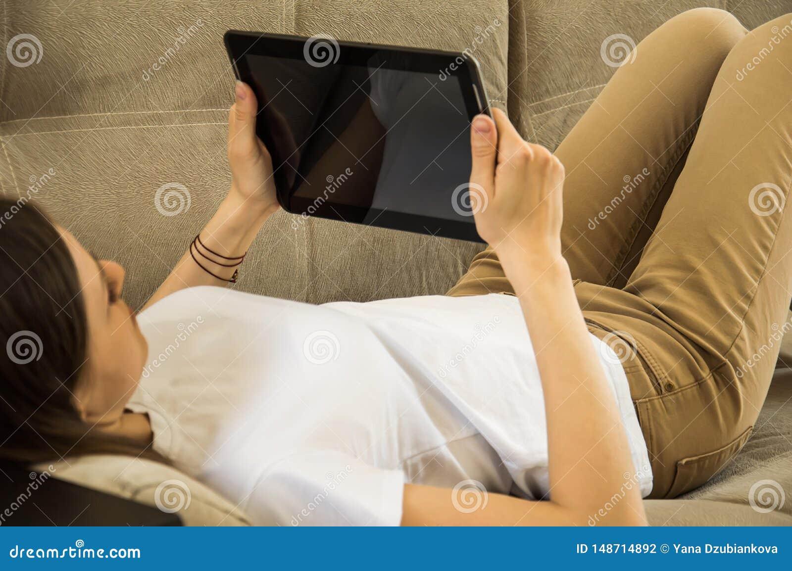 Το κορίτσι βρίσκεται στον καναπέ και διαβάζει τις ειδήσεις και τα μηνύματα στην ταμπλέτα