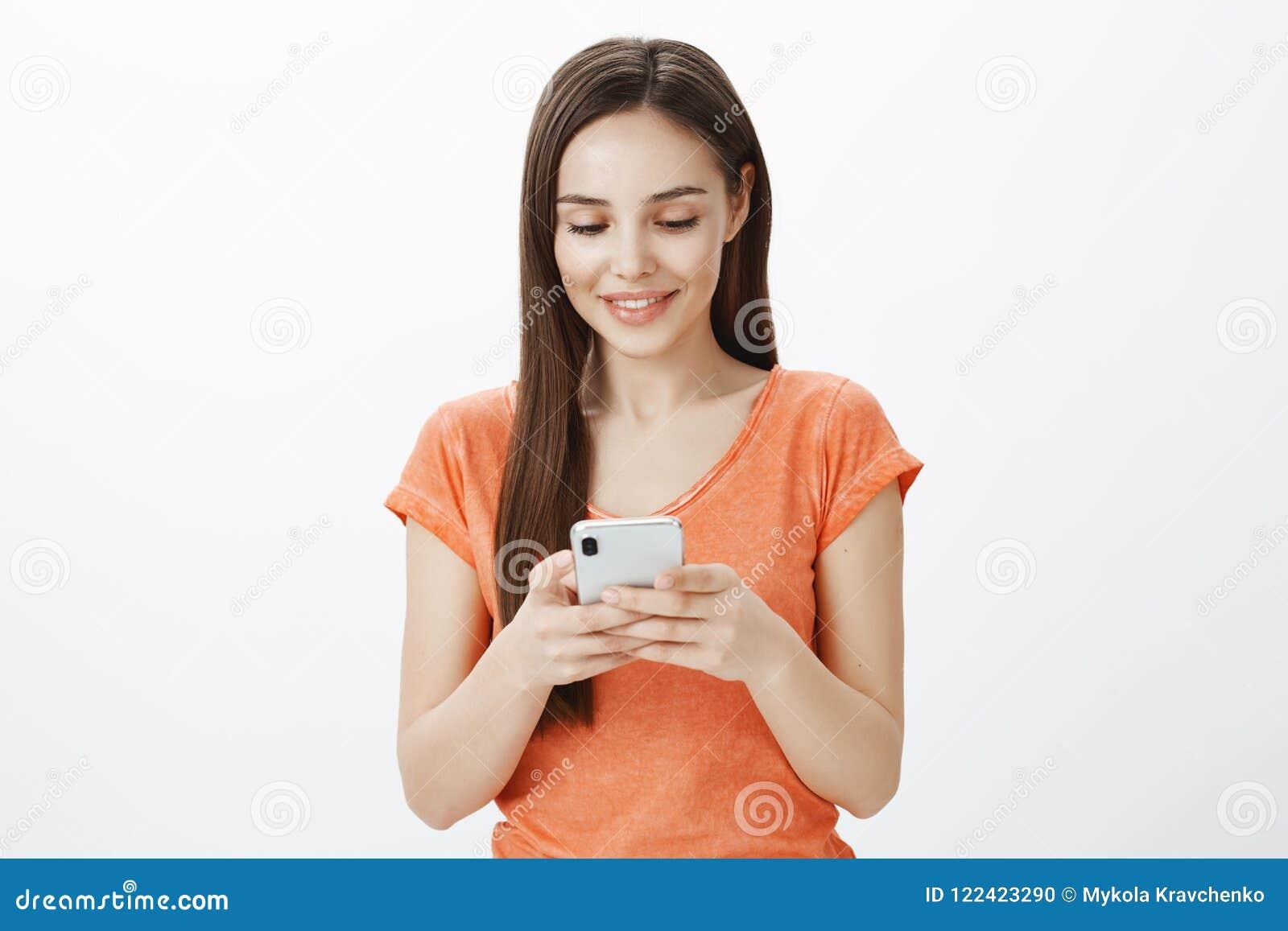 Το κορίτσι διαβάζει το χαριτωμένο μήνυμα στο φίλο, που μένει καταπληκτικό με τις γλυκές λέξεις Εσωτερικός πυροβολισμός της ευτυχο