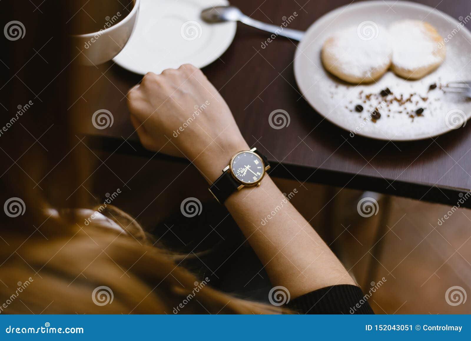 Το κορίτσι εξετάζει το ρολόι σε έναν καφέ πέρα από ένα φλιτζάνι του καφέ χρόνος στο ρολόι - ο χρόνος για το πρόγευμα, επιδόρπιο