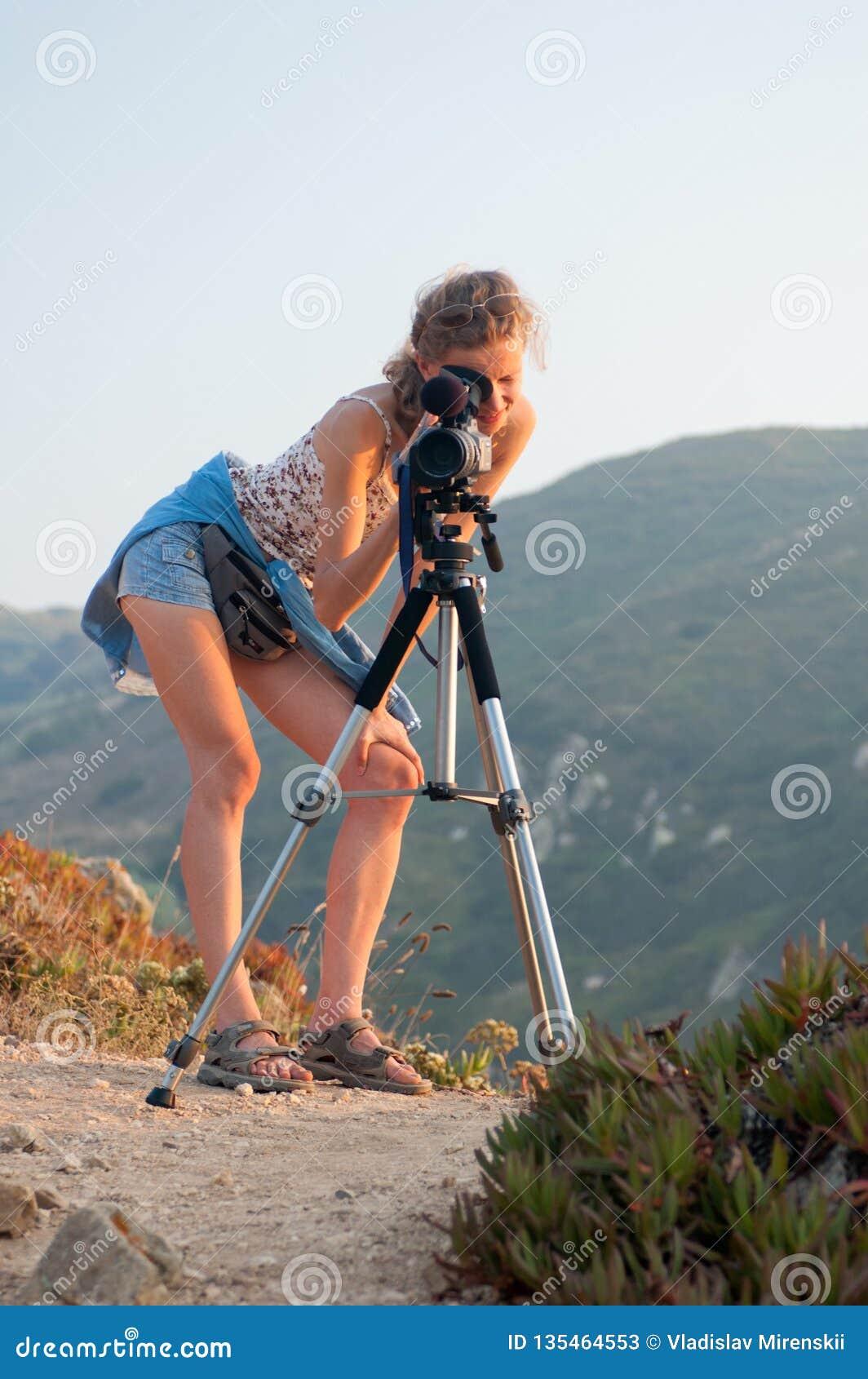Το κορίτσι εξετάζει τη κάμερα που τοποθετείται σε ένα τρίποδο σε ένα υπόβαθρο των πράσινων δασωδών βουνών μια ηλιόλουστη θερινή η