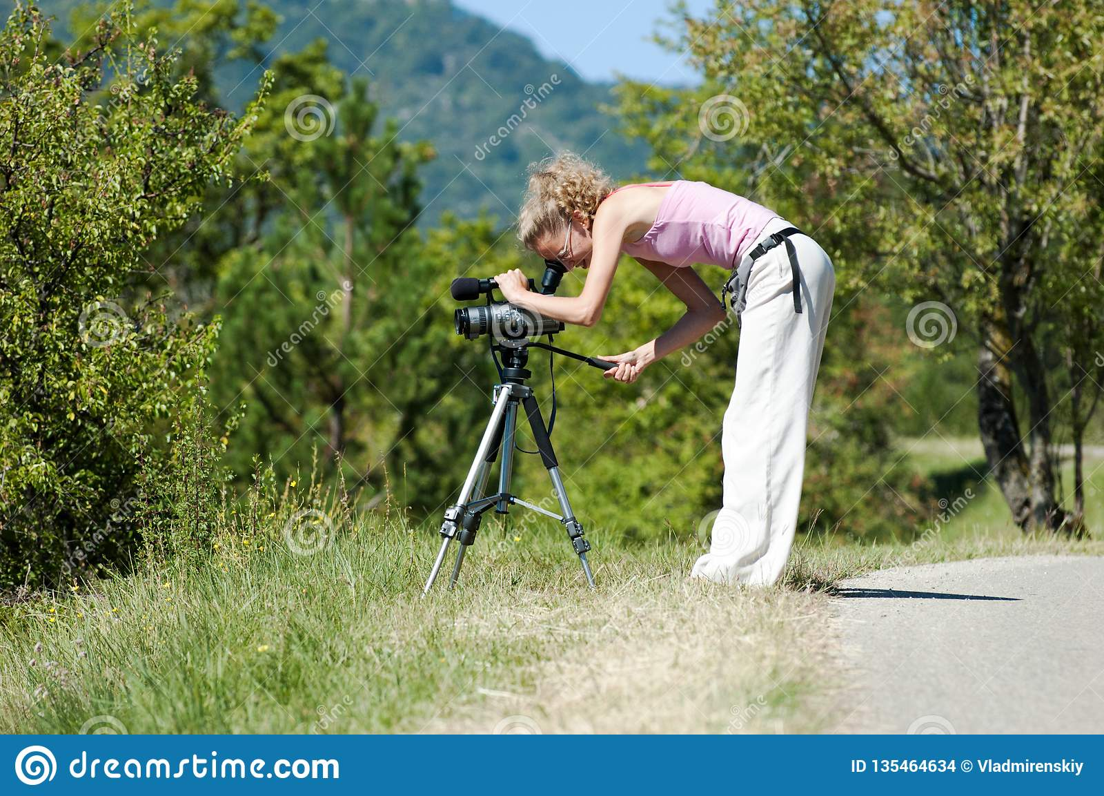 Το κορίτσι εξετάζει τη κάμερα σε ένα τρίποδο στο υπόβαθρο των πράσινων δέντρων και των βουνών μια ηλιόλουστη θερινή ημέρα