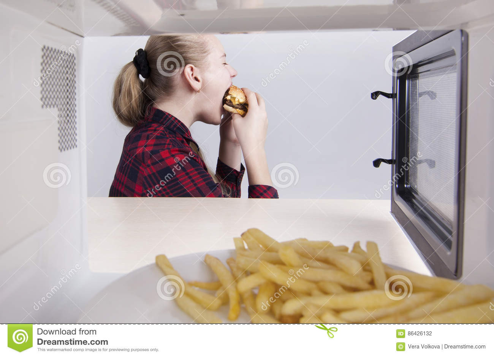 Το κορίτσι εφήβων τρώει λαίμαργα το στόμα χάμπουργκερ ευρέως ανοικτό Κάθισμα στον πίνακα κοντά στο μικρόκυμα Άποψη μέσω του ανοικ