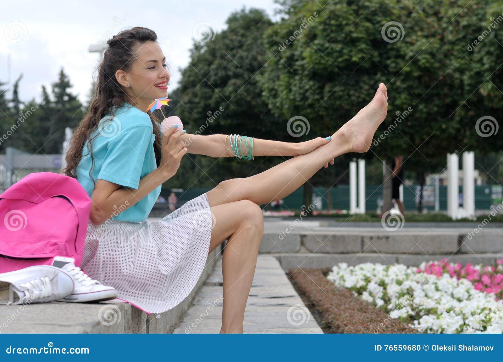 Το κορίτσι κάθεται στα σκαλοπάτια κρατώντας το πόδι της