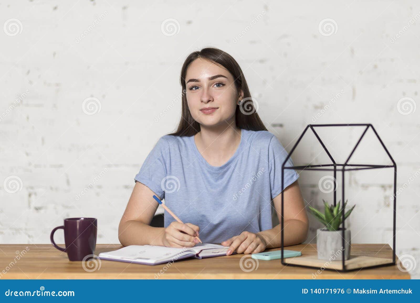 Το κορίτσι κάθεται στον πίνακα και κοιτάζει άμεσα Κρατά ένα μολύβι Στον πίνακα αξίζει ένα φλυτζάνι