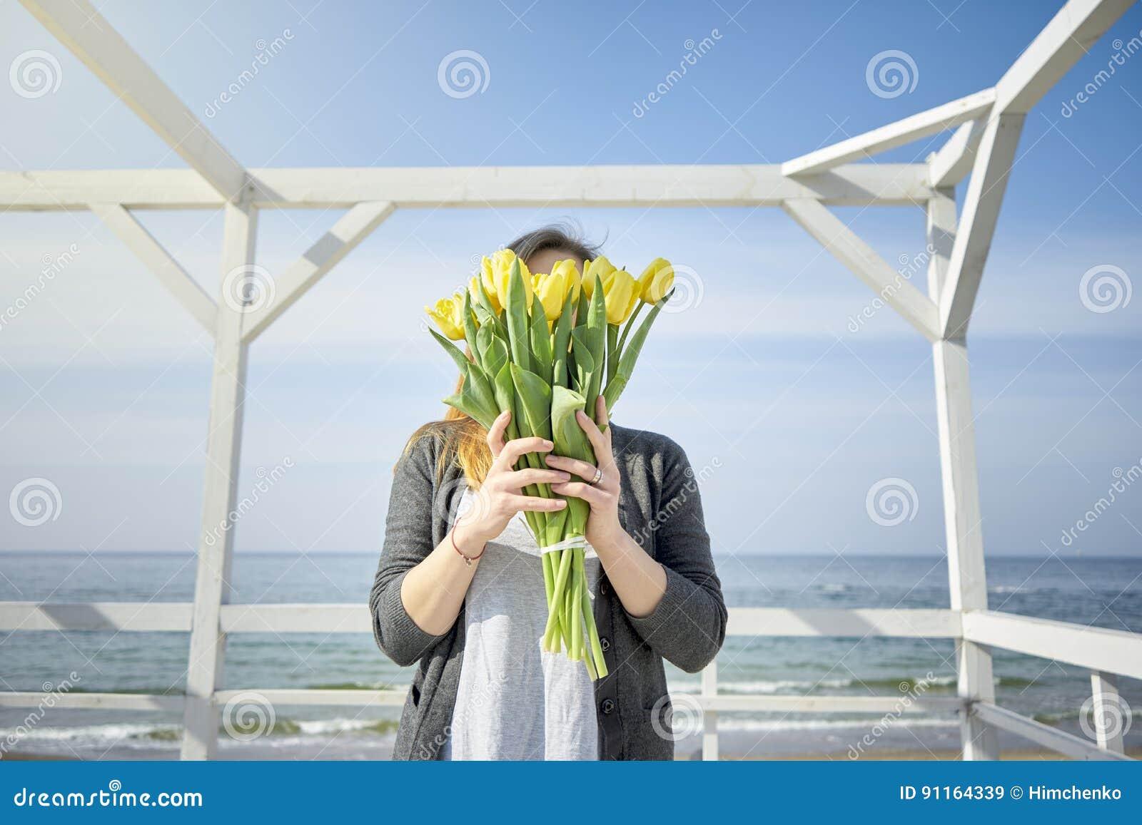 Το κορίτσι καλύπτει το πρόσωπό της με τις κίτρινες τουλίπες