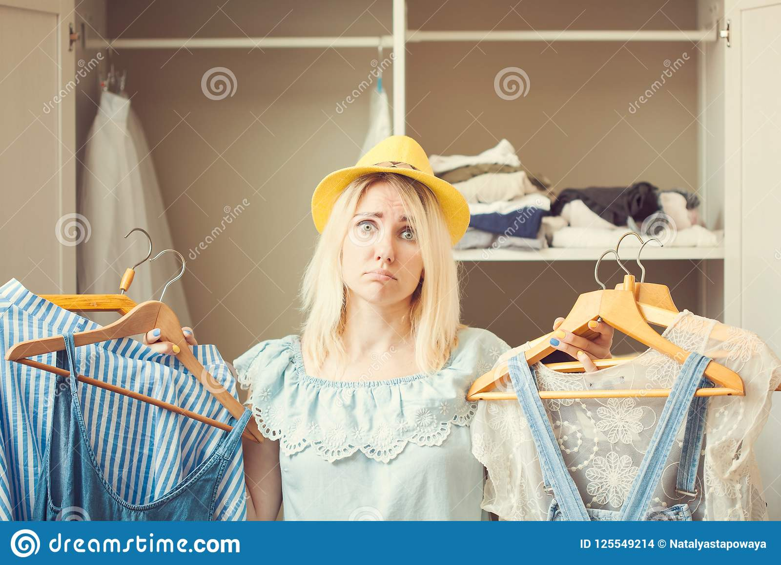 Το κορίτσι κοντά σε μια ντουλάπα με τα ενδύματα δεν μπορεί να επιλέξει τι να φορέσει Η βαριά έννοια επιλογής δεν έχει τίποτα που