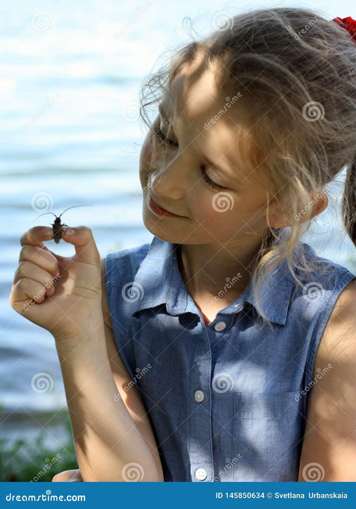 Το κορίτσι κρατά έναν κάνθαρο σε ετοιμότητα