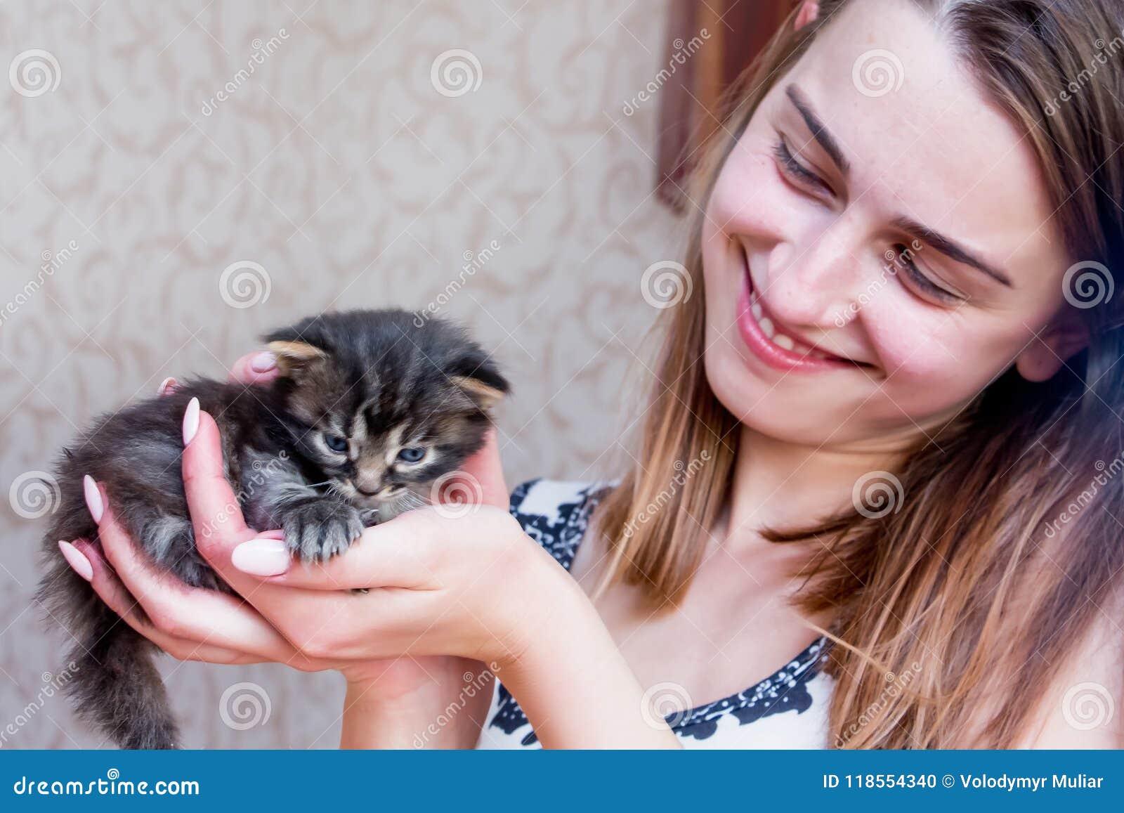 Το κορίτσι κρατά ένα μικρό γατάκι σε ετοιμότητα της Λίγο γατάκι στο ασφαλές χ