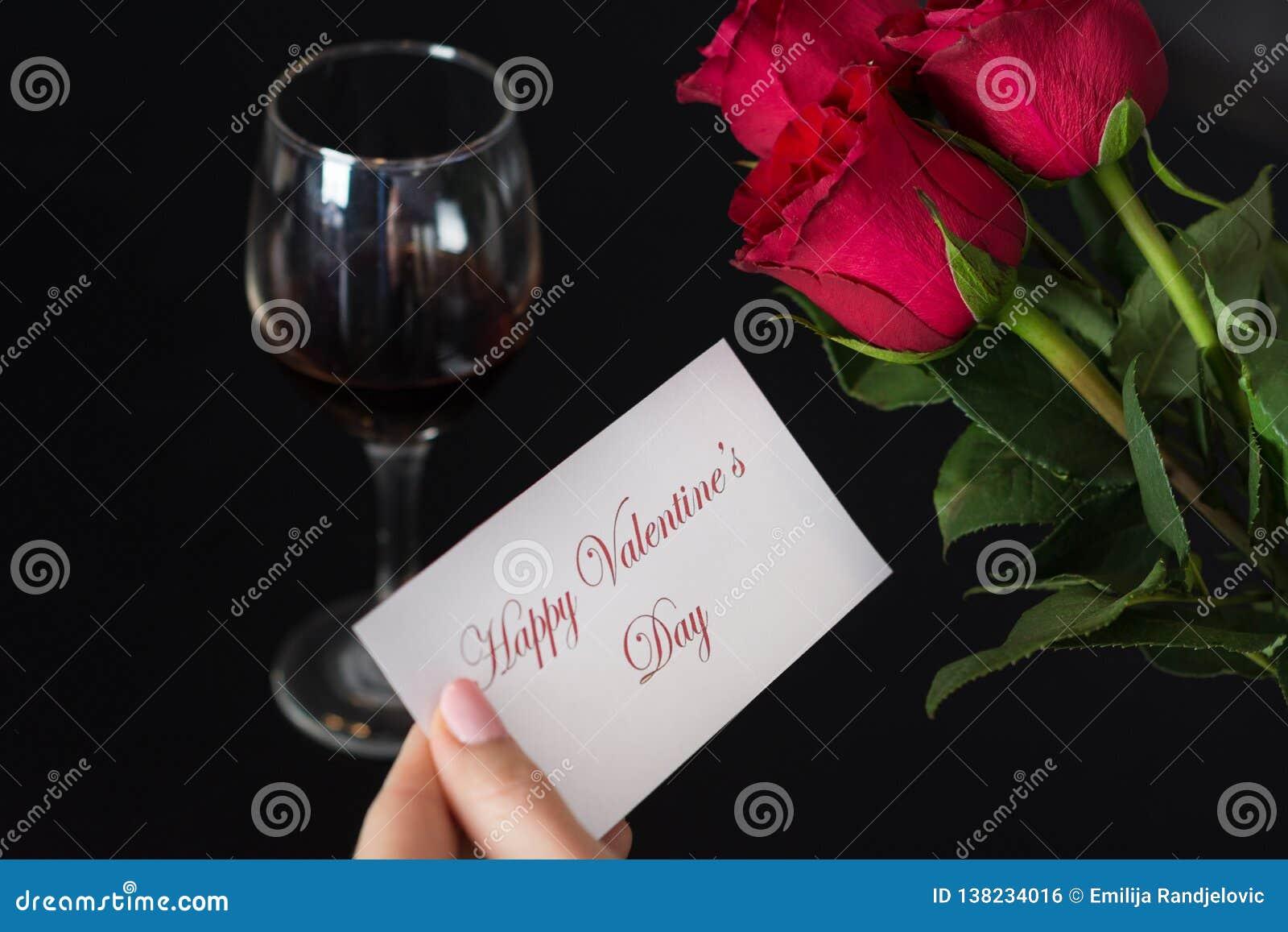 Το κορίτσι κρατά μια κάρτα εγγράφου με μια ευτυχή ημέρα βαλεντίνων μηνυμάτων στο χέρι της και κόκκινος αυξήθηκε και γυαλί κρασιού